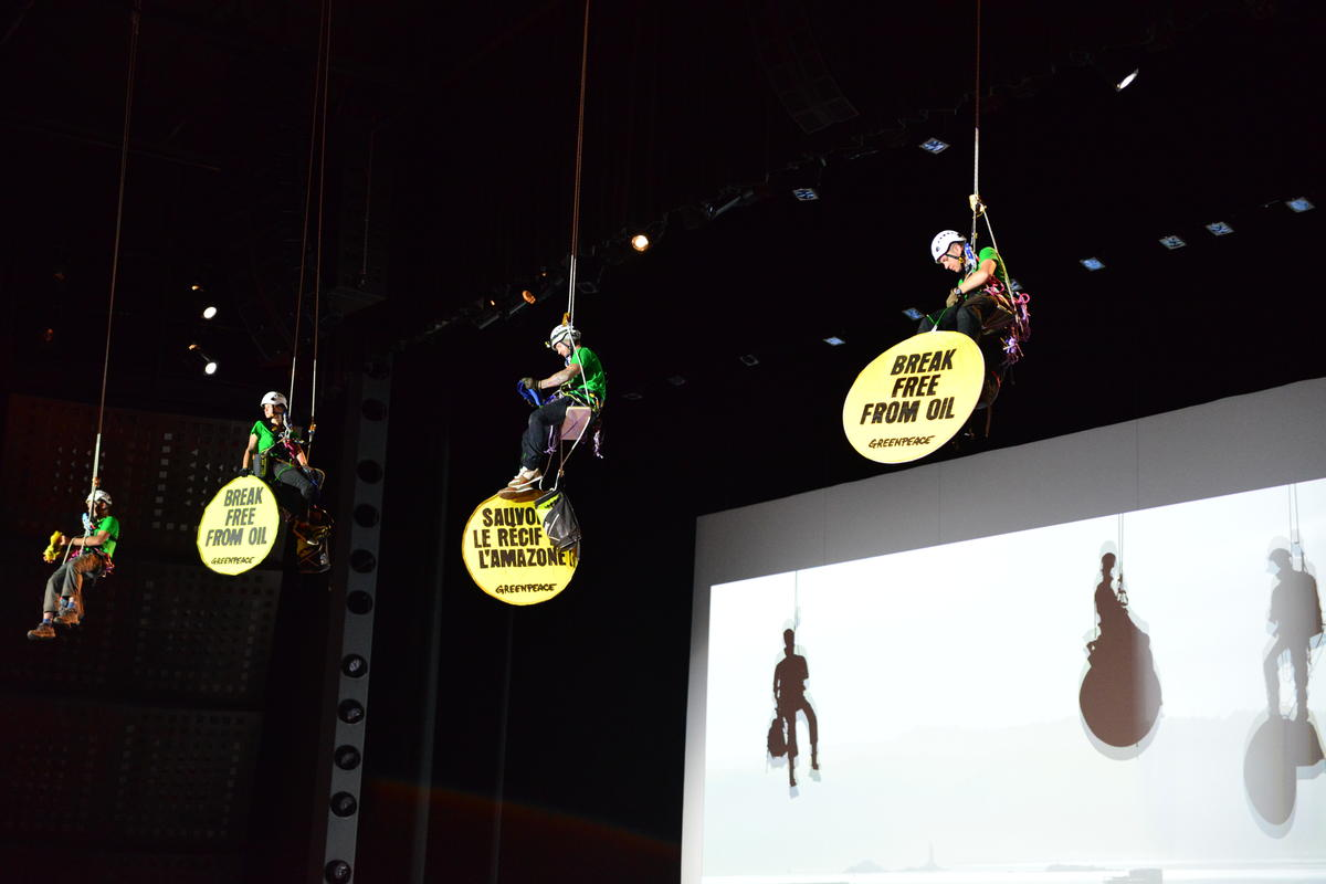 Three activists in climbing gear from the ceiling of a large auditorium, holding circular signs with campaign slogans in multiple languages.