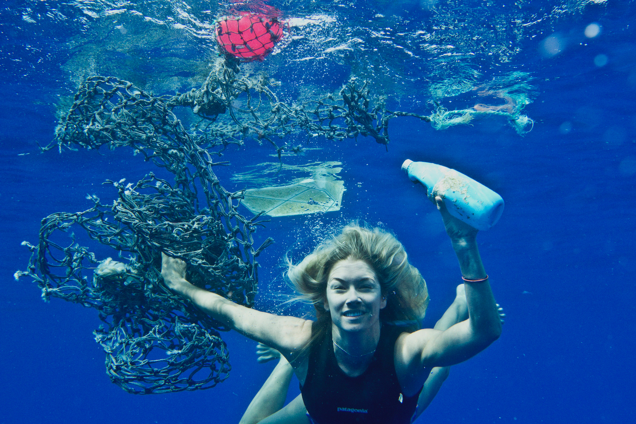 Woman diving underwater holding plastic bottles and other waste
