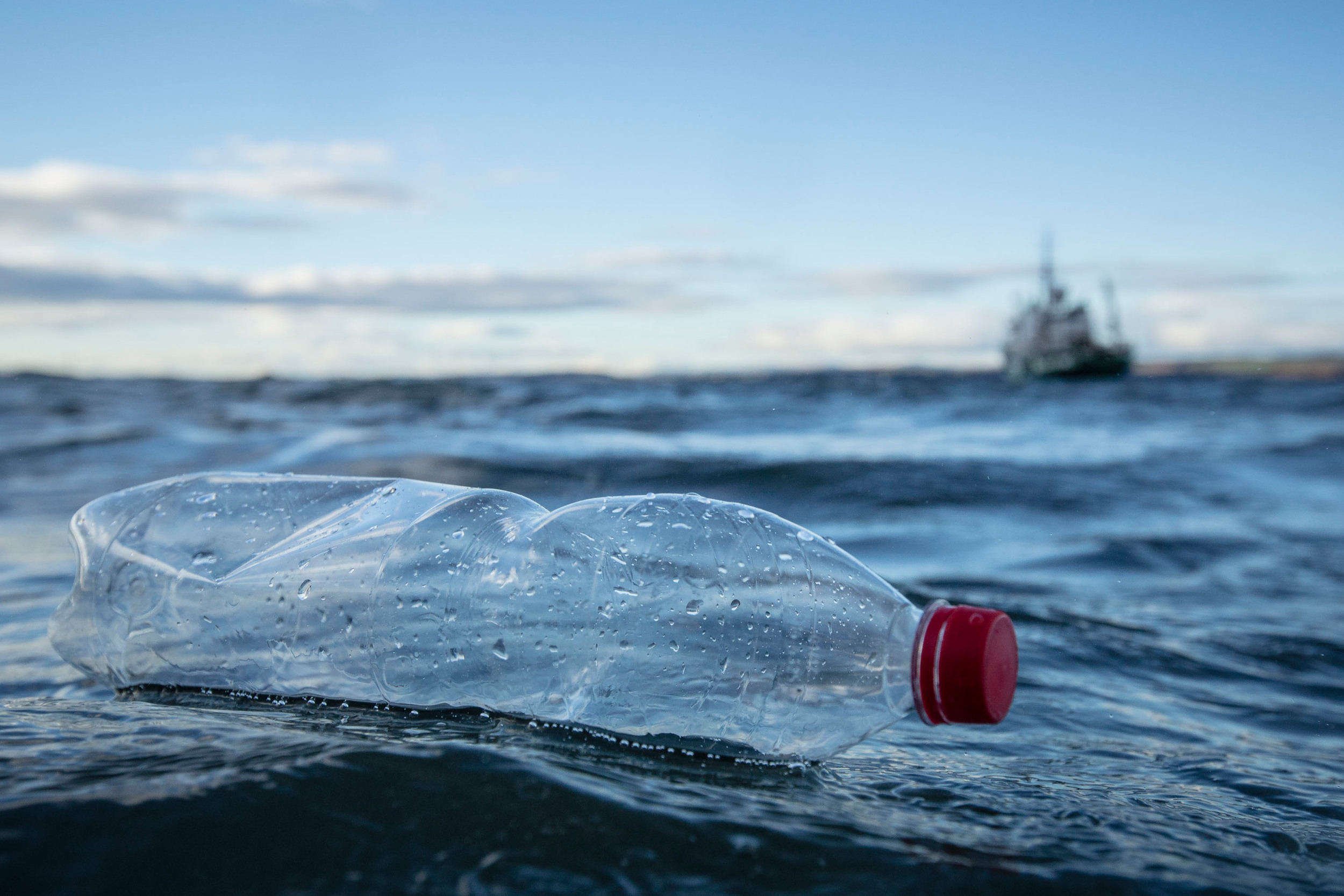 Plastic bottle in the water on a beach with a boat in the background