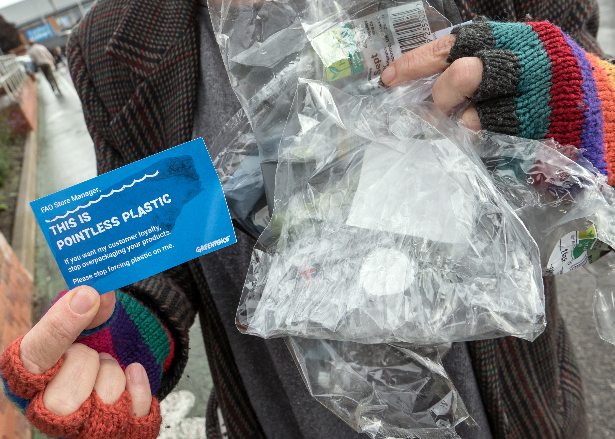 Close up of someone's hands holding plastic packaging and a Greenpeace flyer with a note to supermarket store managers