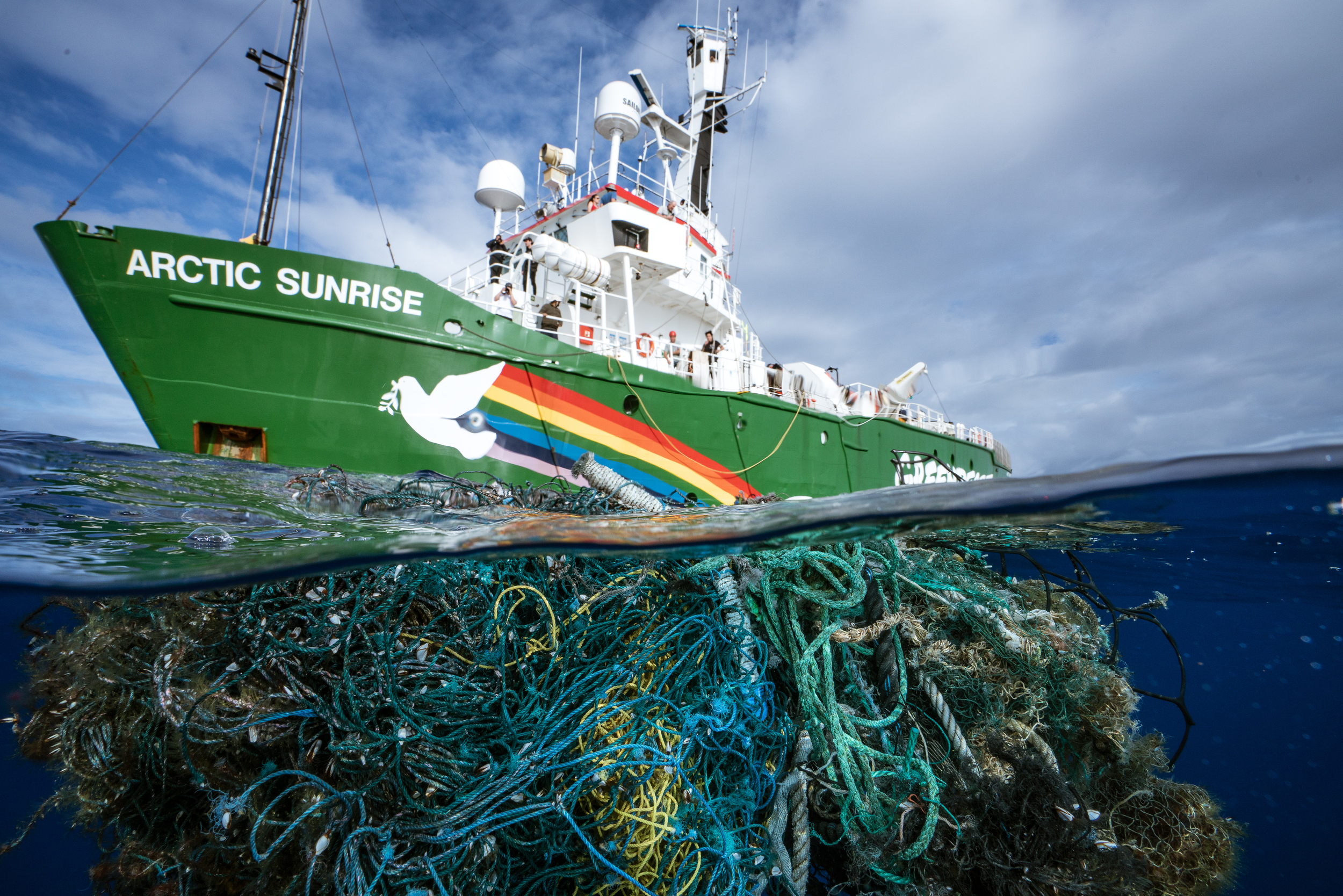 Debris from a fishing net seen underwater with MY Arctic Sunrise ship in background.
