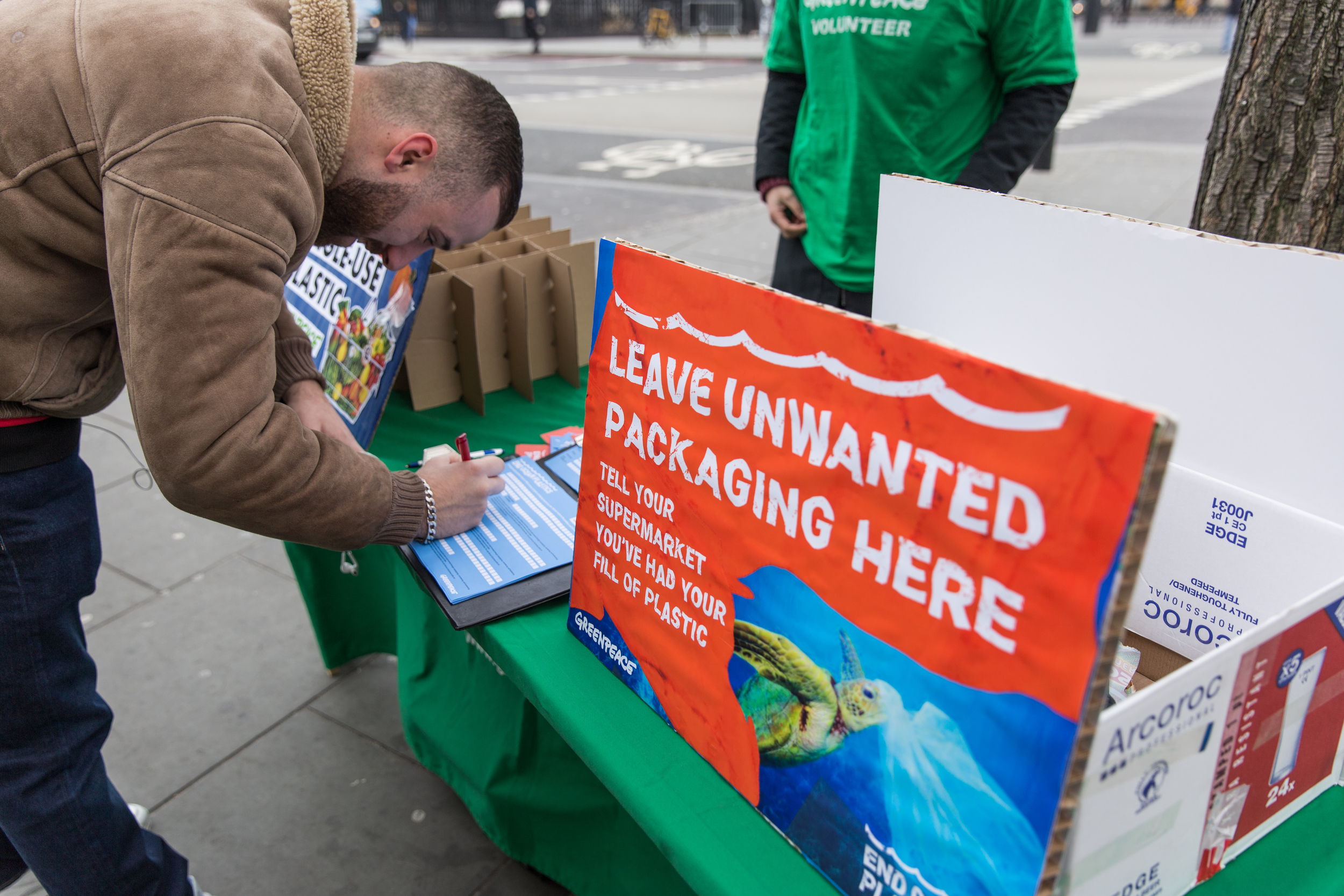 Member of the public signs a greenpeace petition outside a supermarket in London