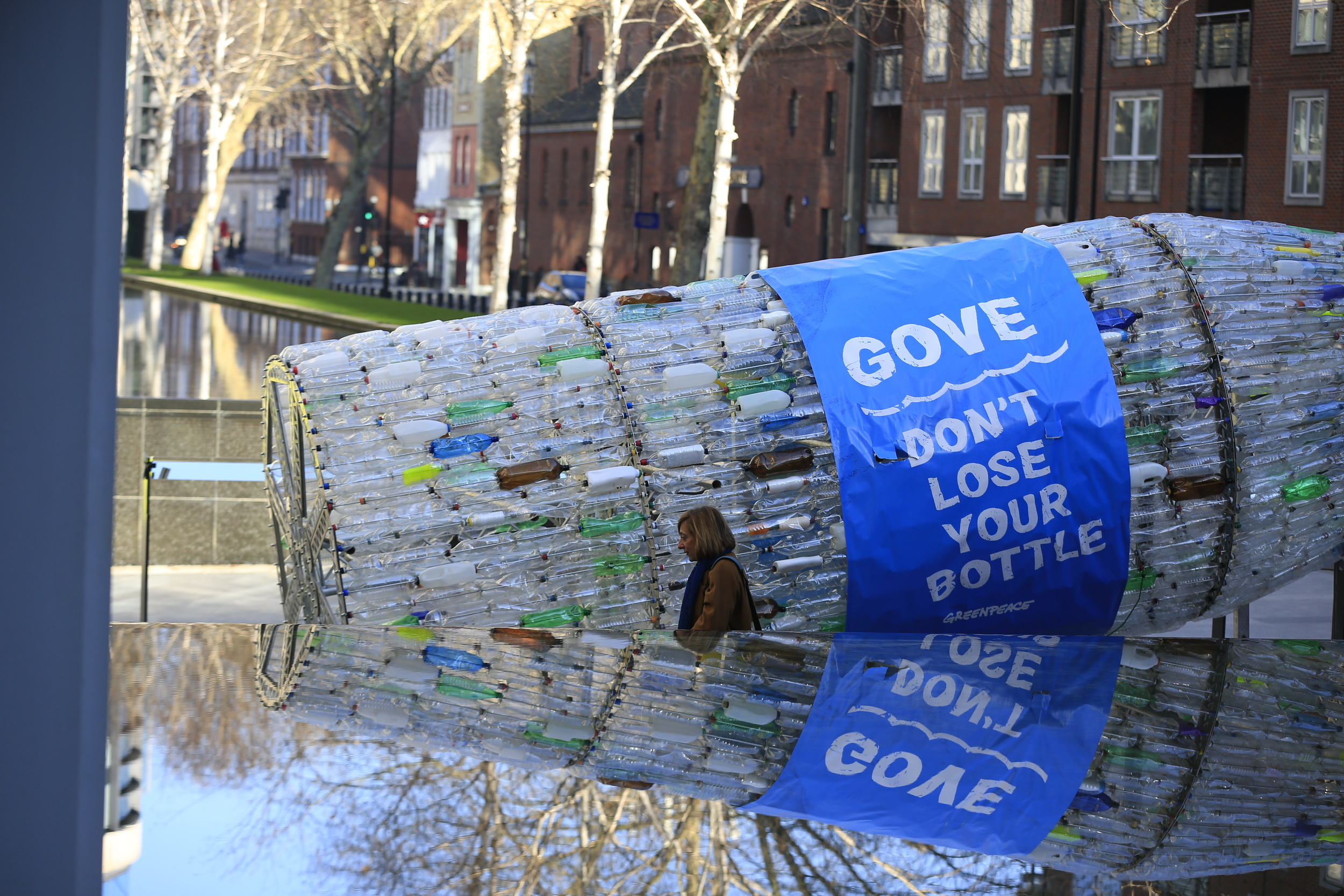Giant sculpture of a plastic bottle made up of hundreds of real plastic bottles is carried through London by volunteers