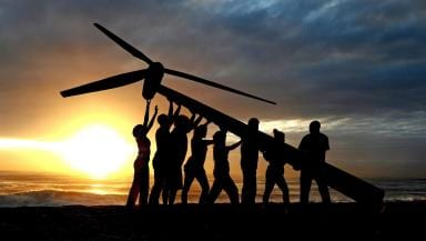 People symbolically raising a Wind Turbine to show the importance of green jobs.