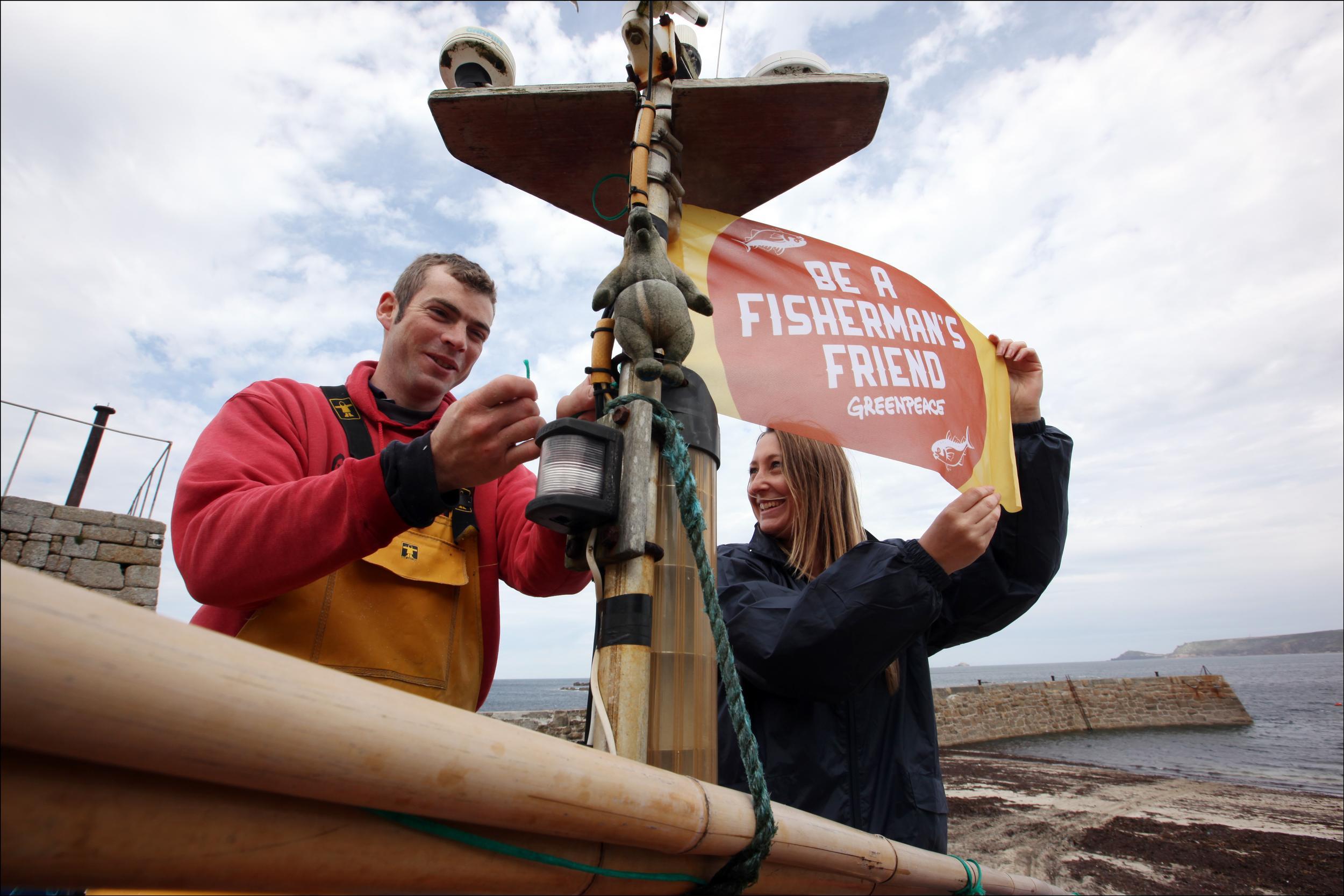 Greenpeace campaigners raise a flag reading