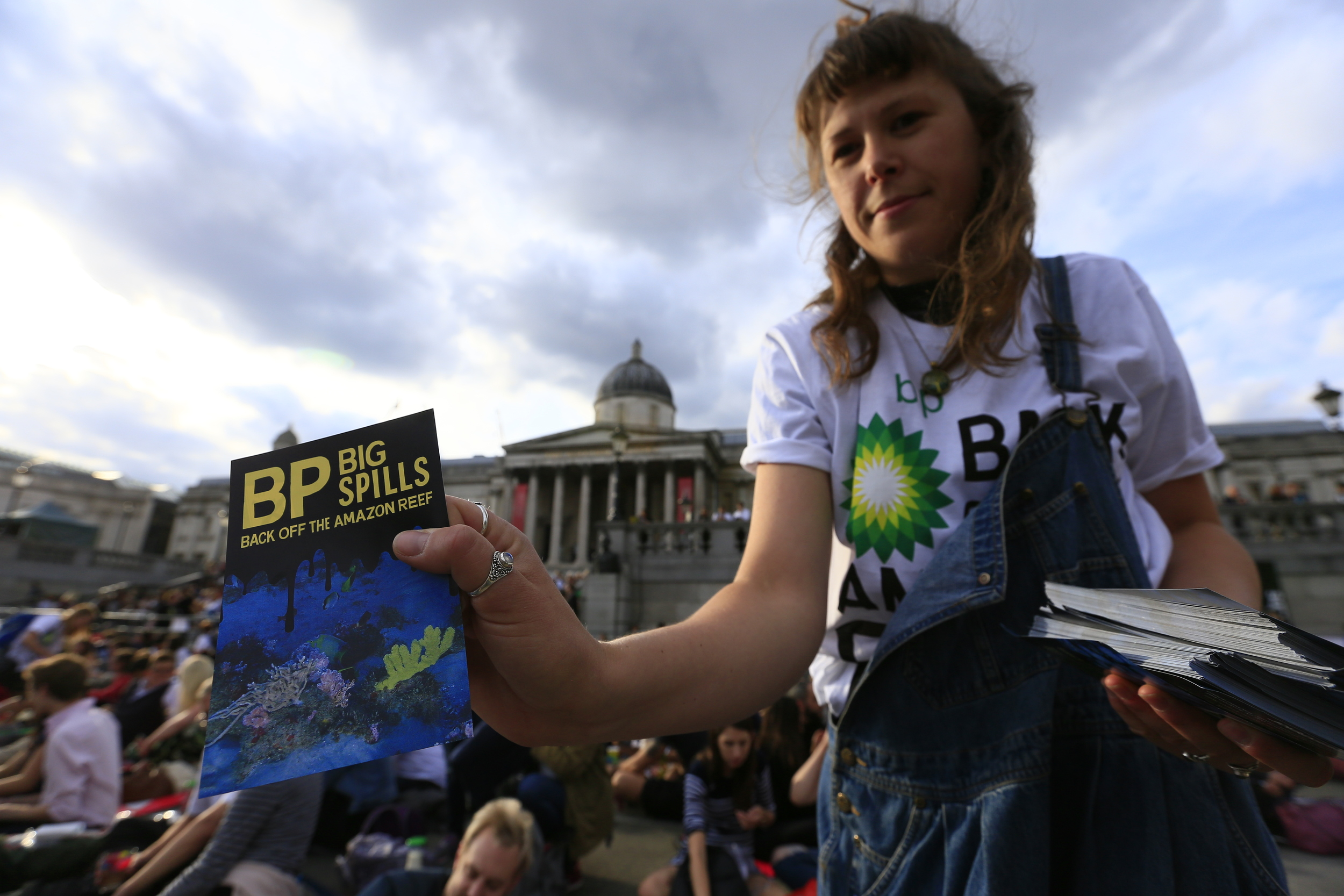 Greenpeace volunteers distribute leaflets on Trafalgar Square