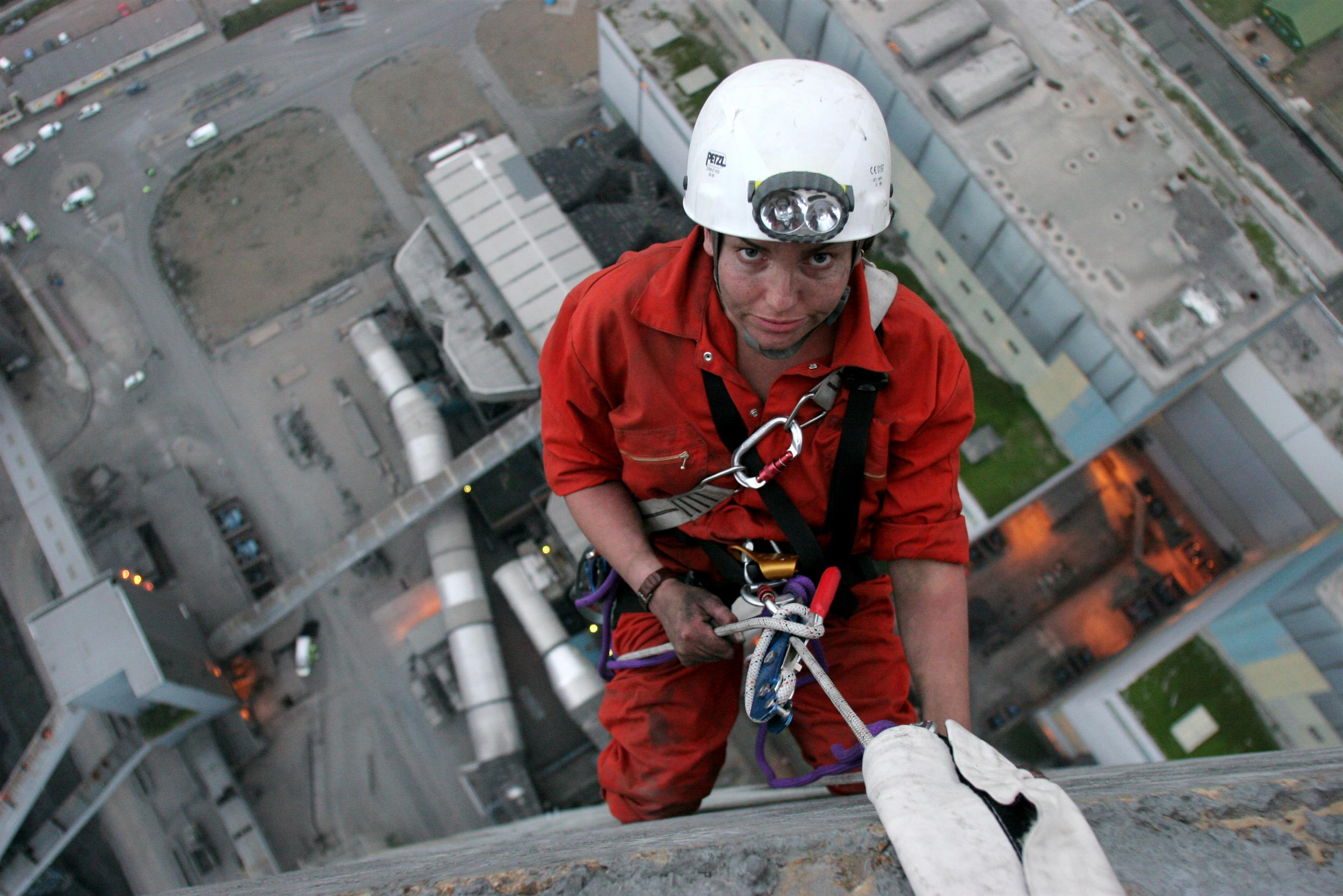 Greenpeace activist looks up while abseiling down Kingsnorth coal-fired power station.