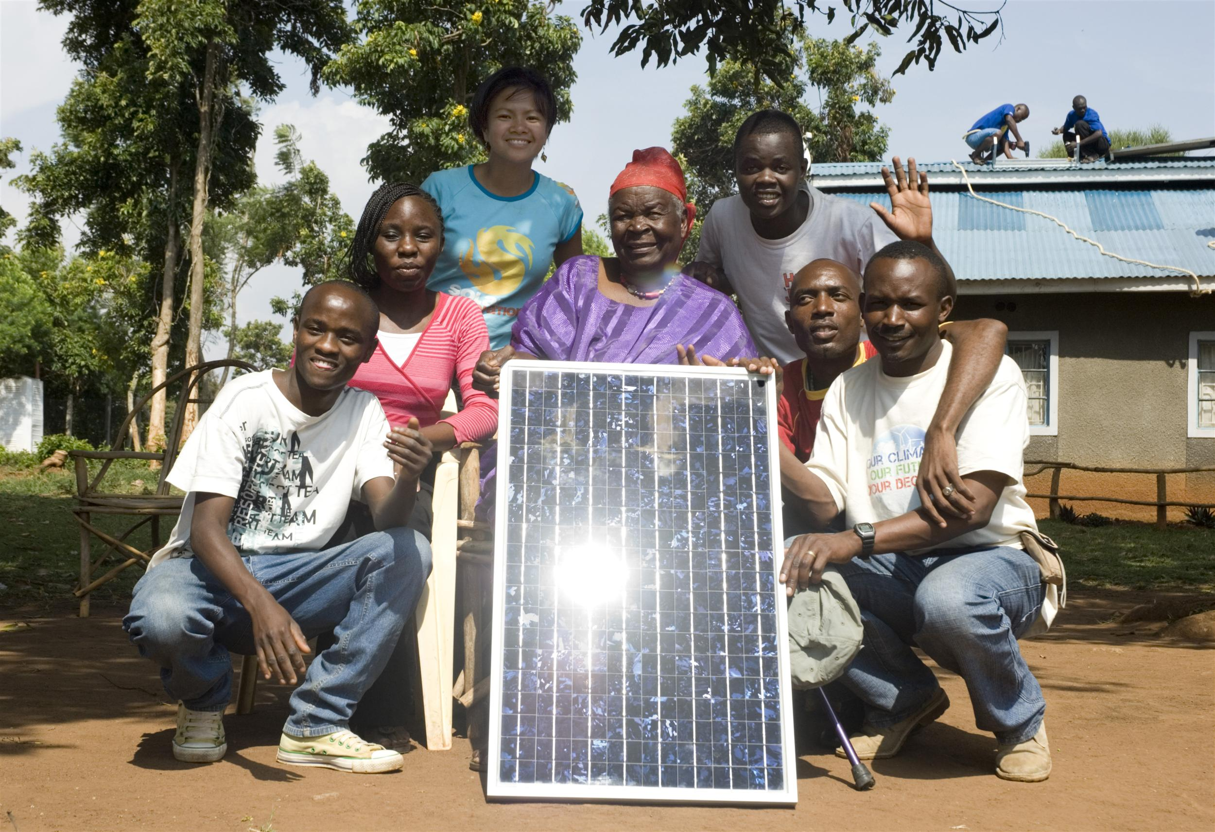 Mama Sara Obama, the US President's grandmother, holds a solar panel while posing for a group photo with solar panels