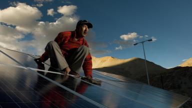 Person sitting on a roof with solar panels