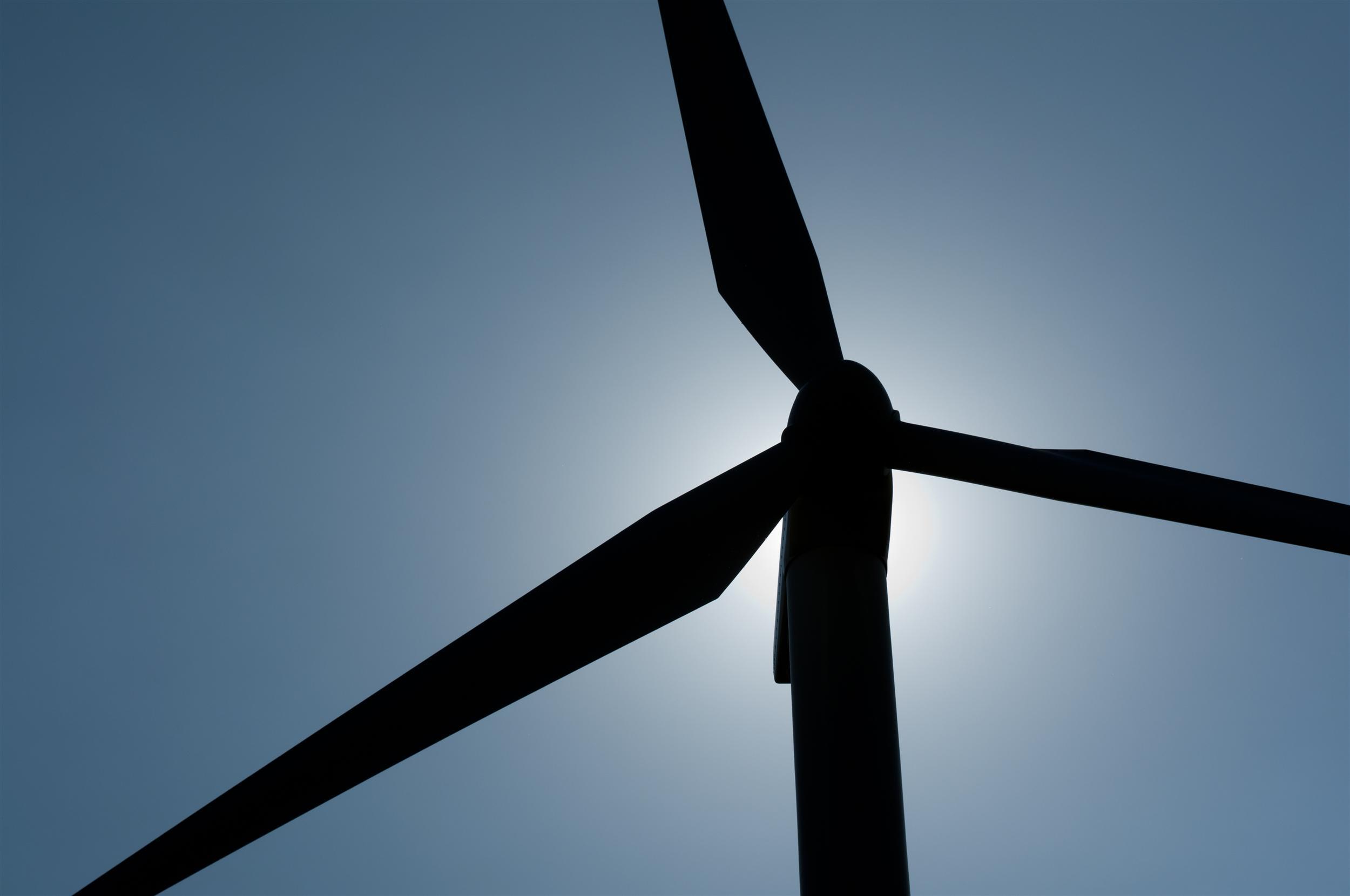 The sun creates a silhouette behind a wind turbine