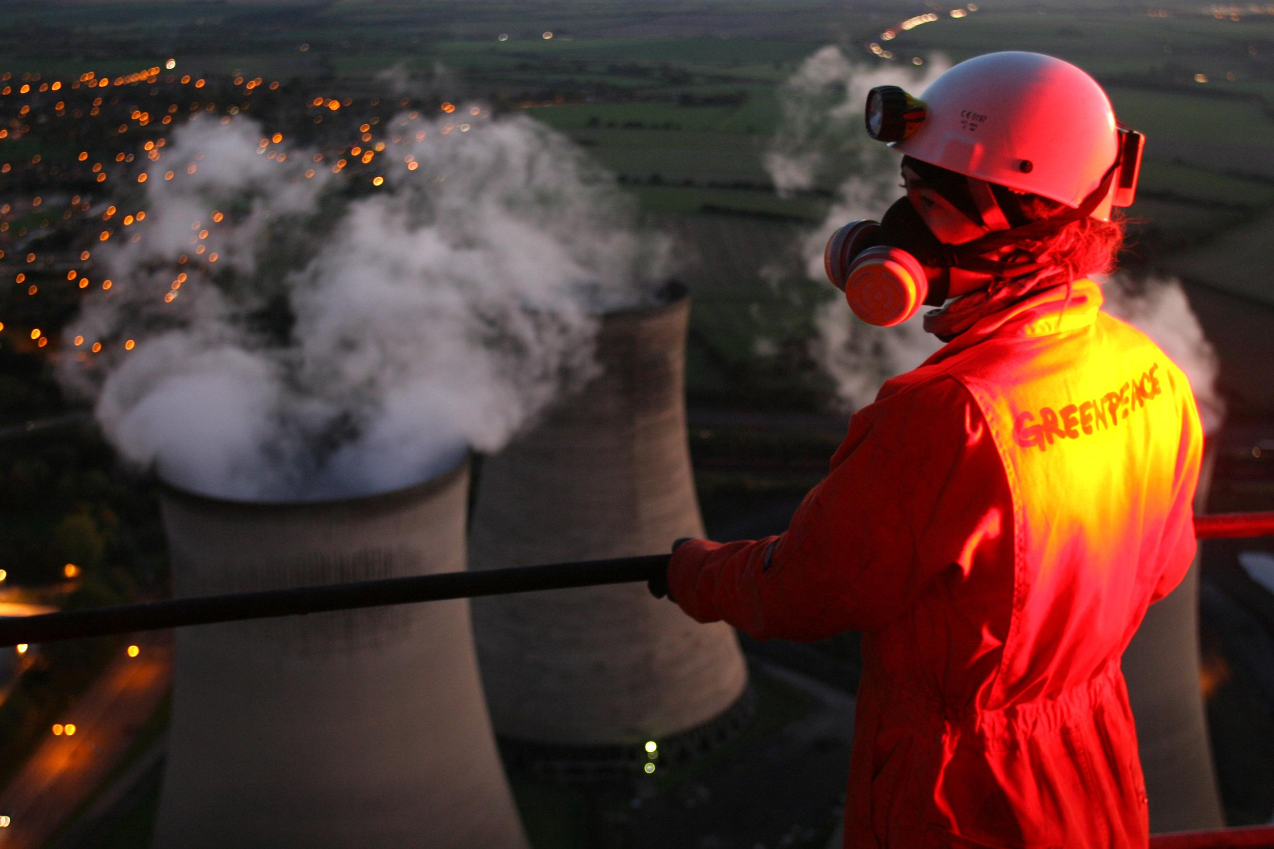 A Greenpeace activist overlooks cooling towers at Didcot power station during a 2 day occupation
