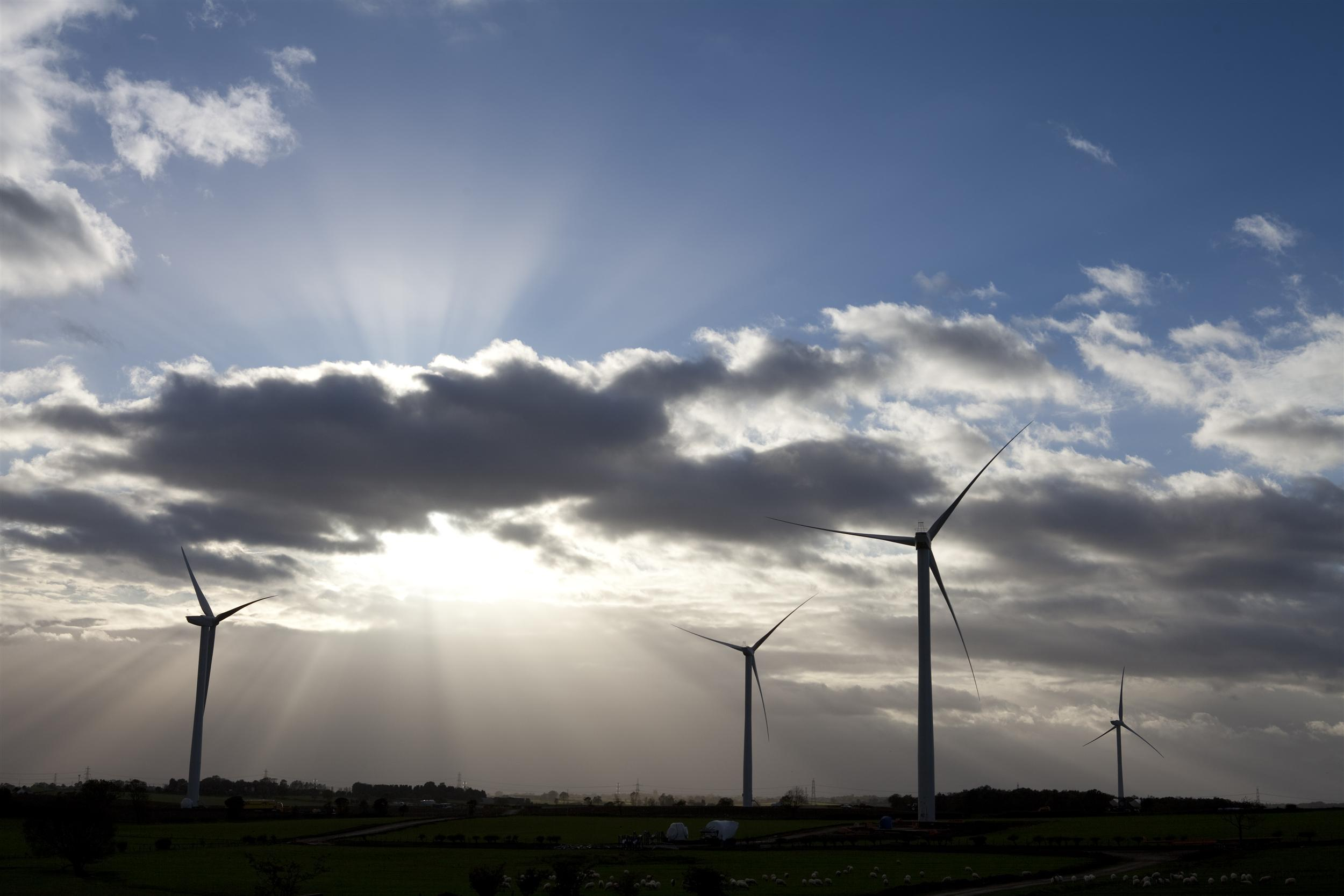 Wind turbines with sunshine and clouds in the background
