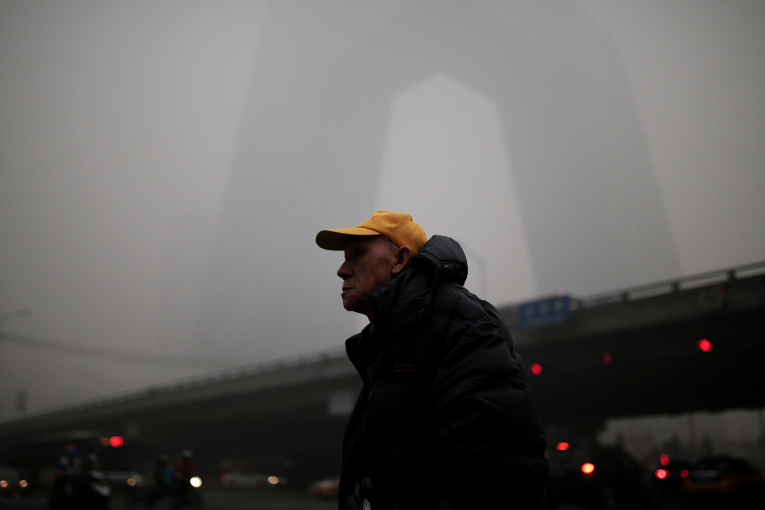 A Beijing resident gazes at the smog