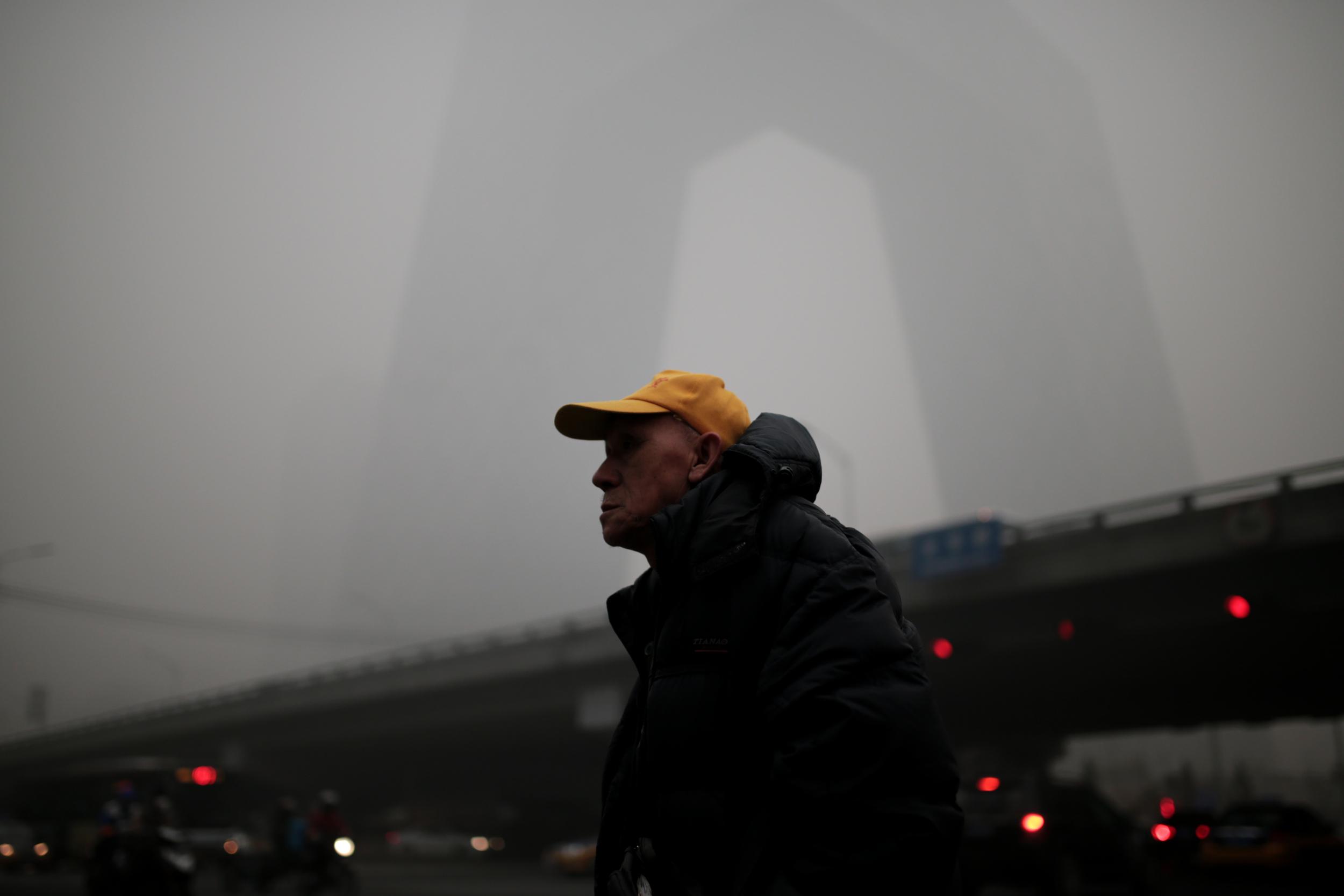 A Beijing resident gazes at the smog