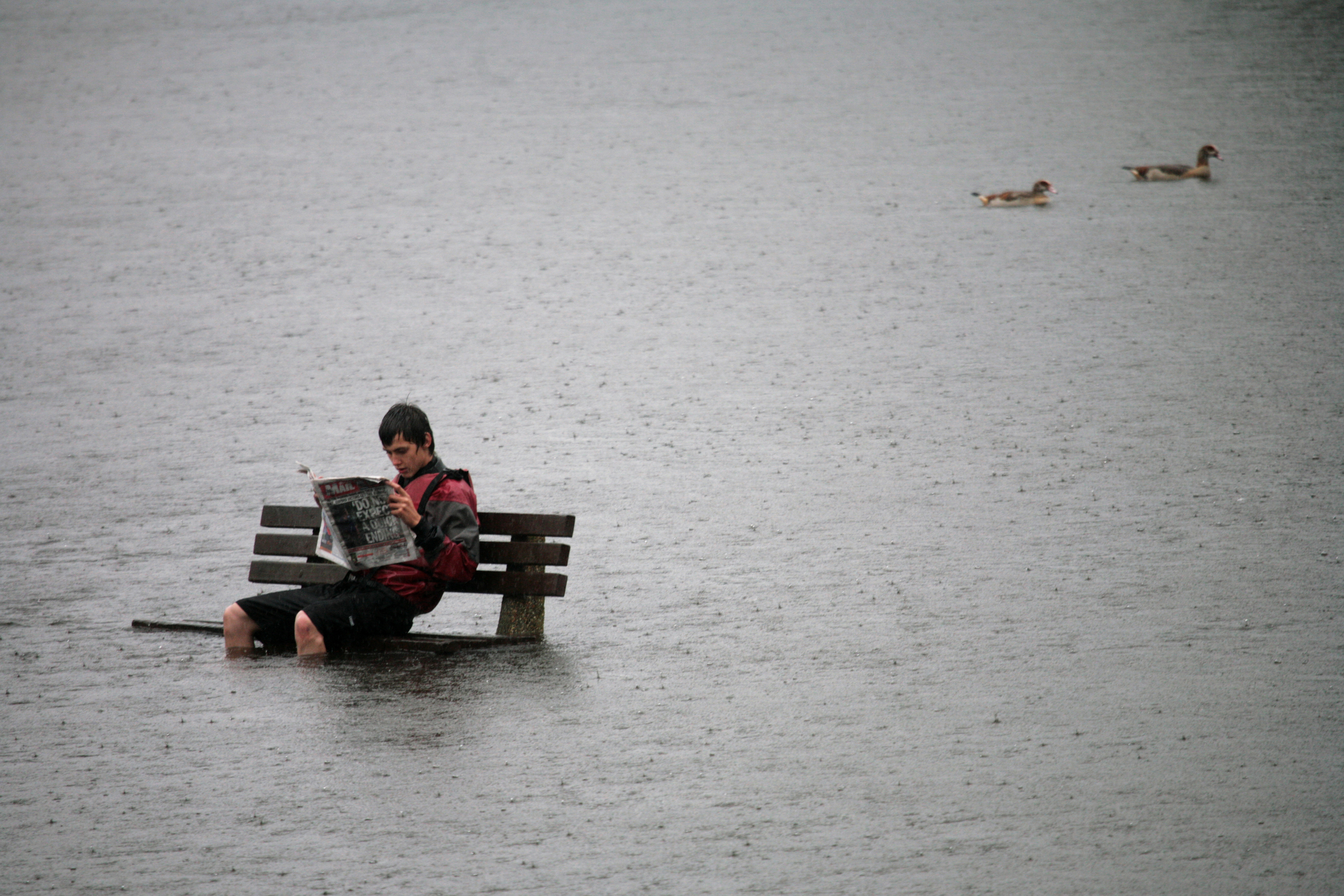 person sitting on bench in flooded area