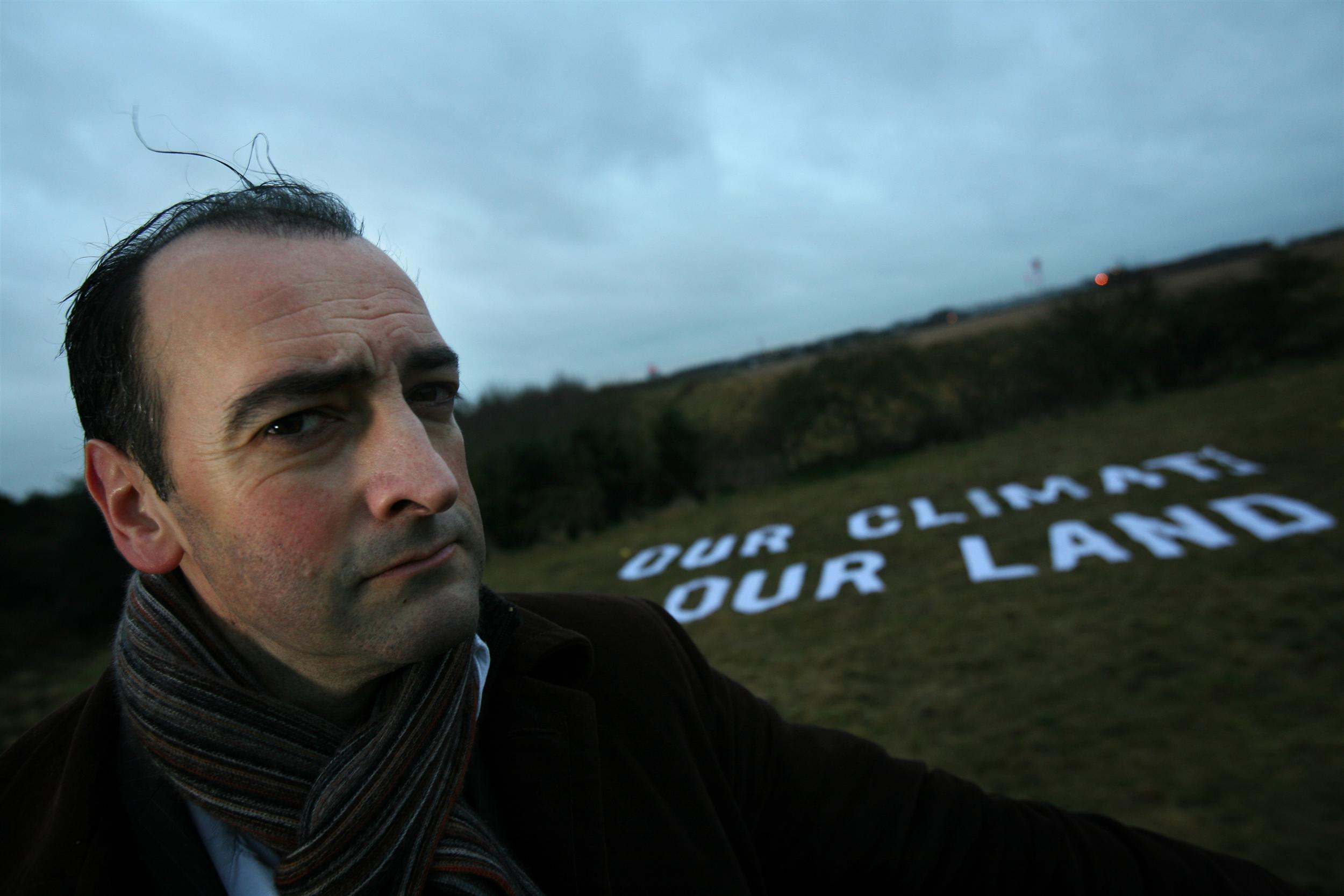 man standing in front of field with 'Our Climate Our Land' message on it