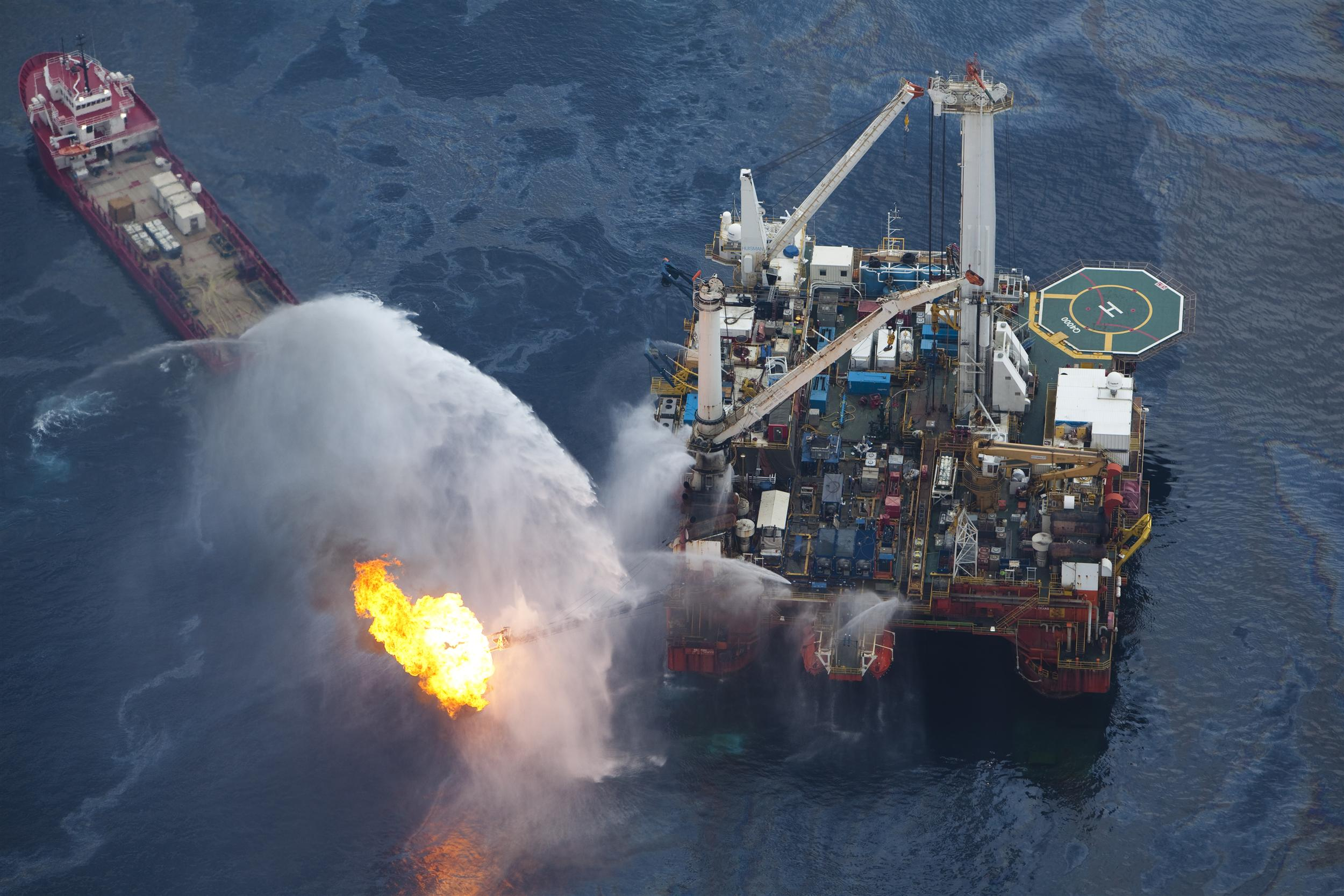 A ship sprays water on the pipe burning off the side of the platform in the Gulf of Mexico