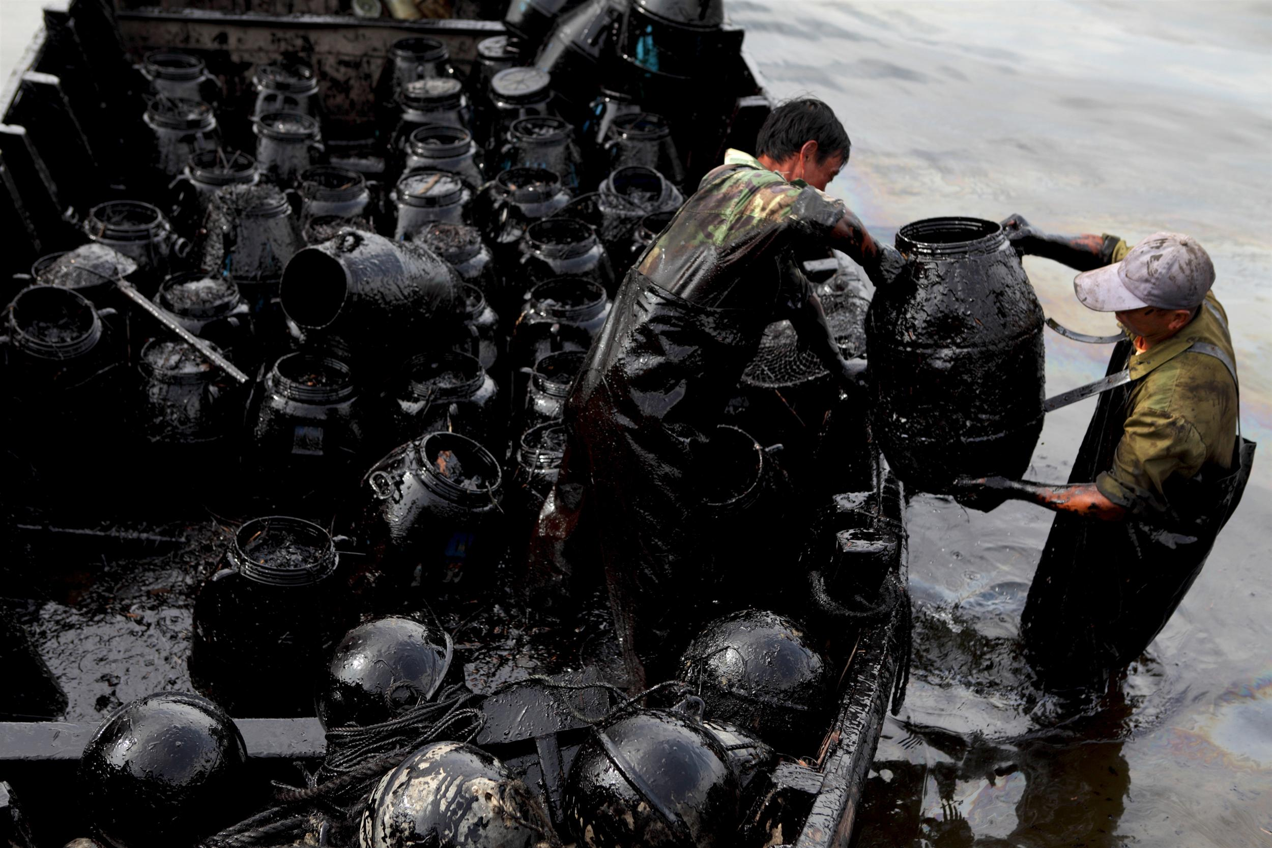 people with oily barrels doing a clean up of an oil spill