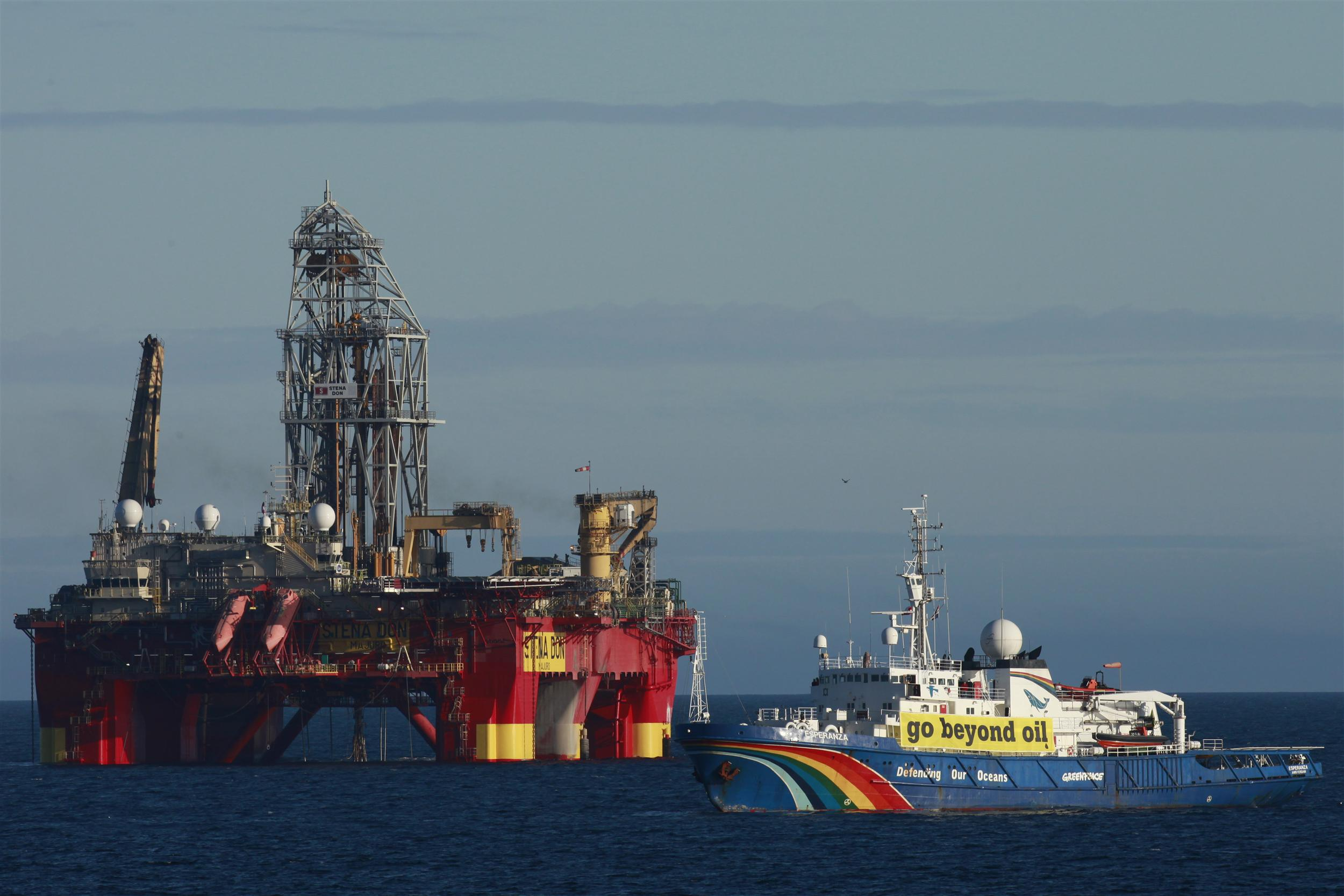greenpeace ship in front of an oil platform