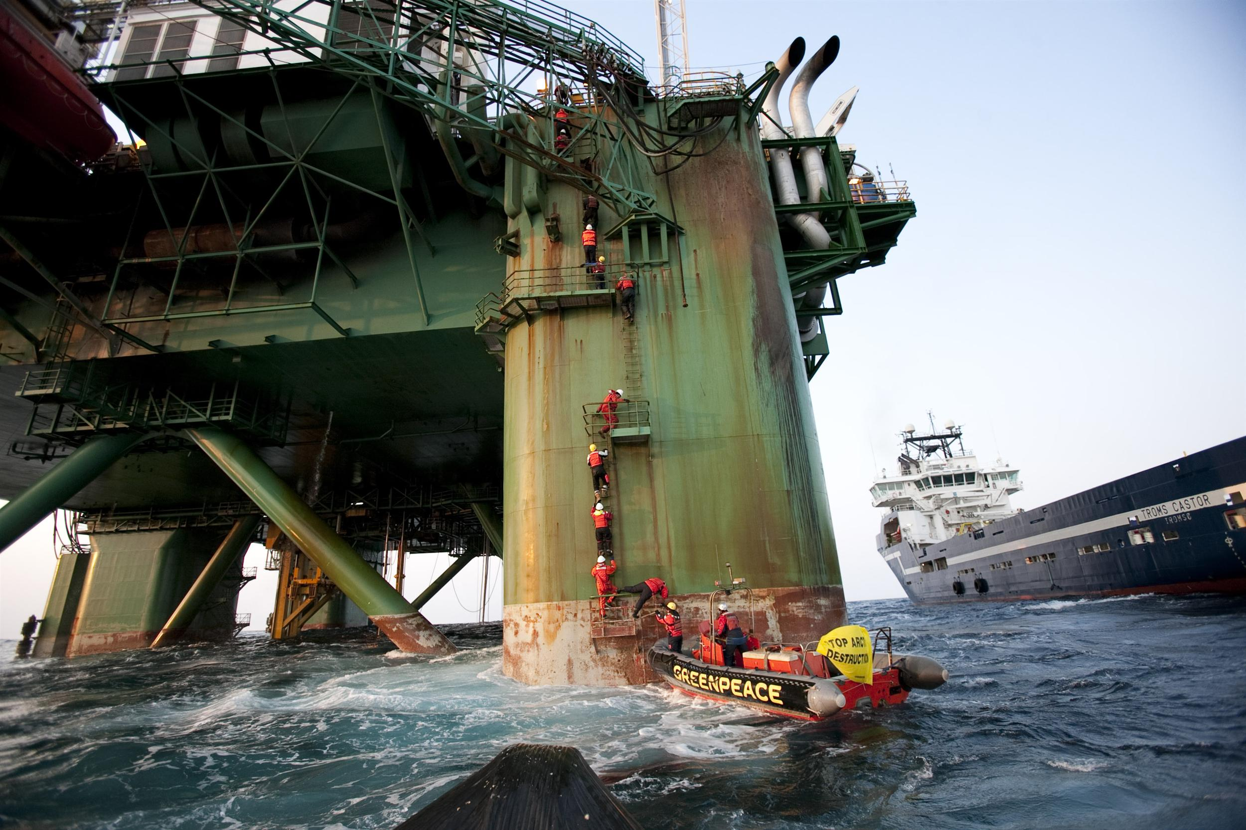 activists climb up an oil rig out of a greenpeace rhib