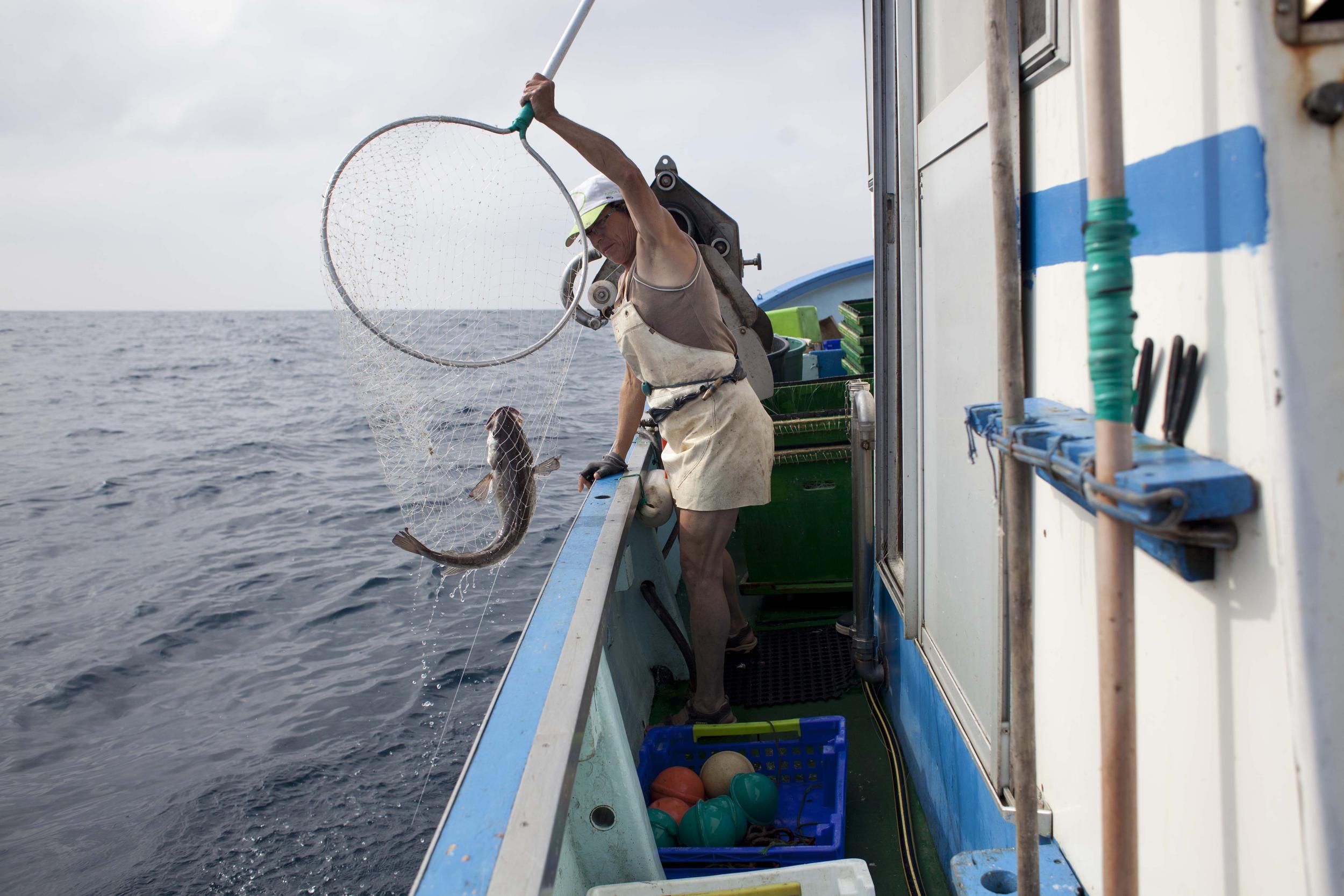 fisherwoman throwing fish overboard