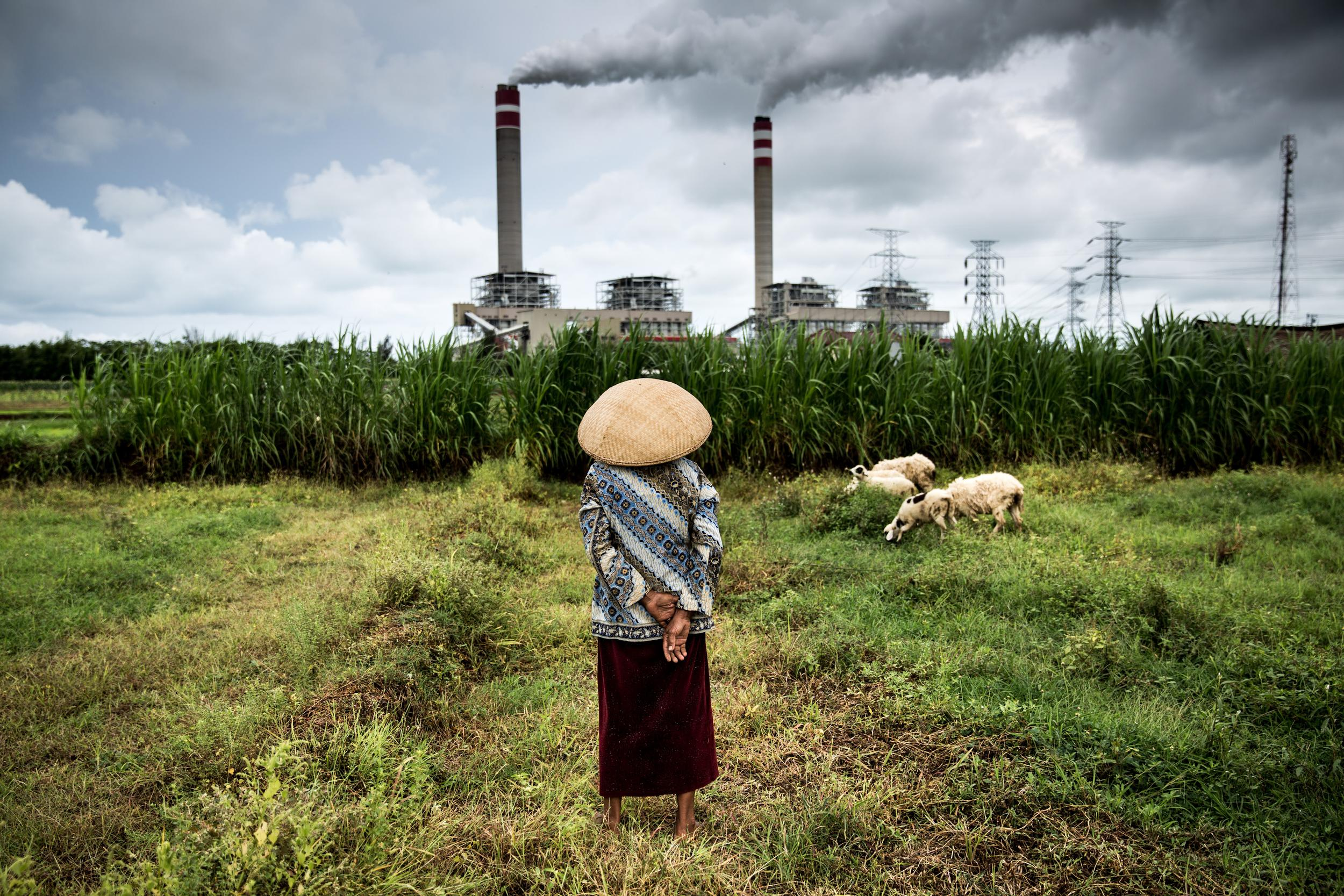 indonesian woman looking at coal power plant