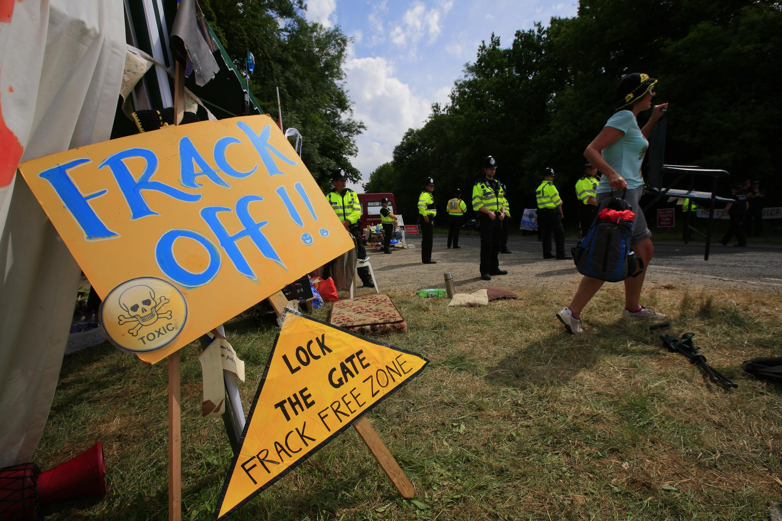 frack off signs and police in a field