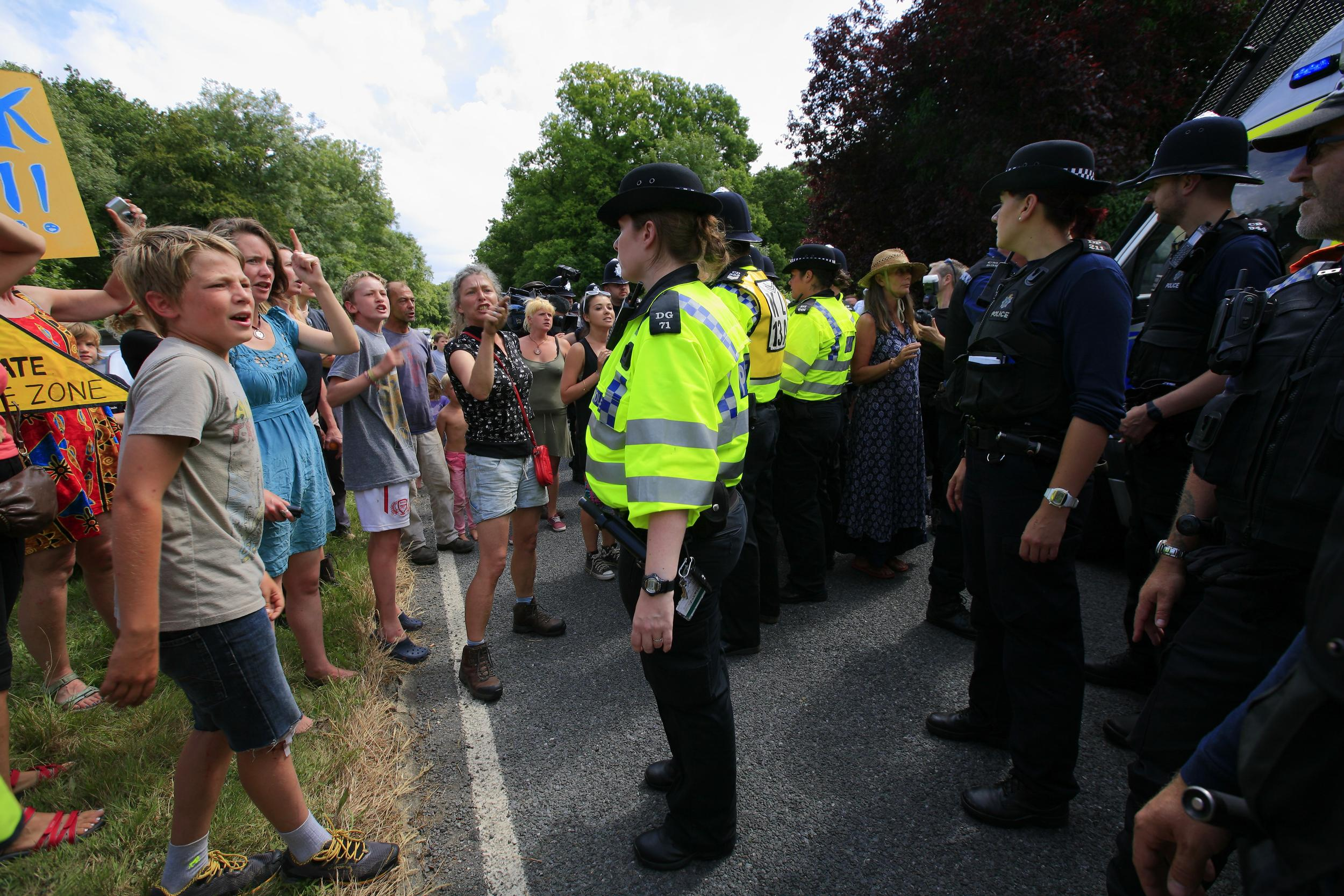 police officers stand face to face with anti-fracking protesters