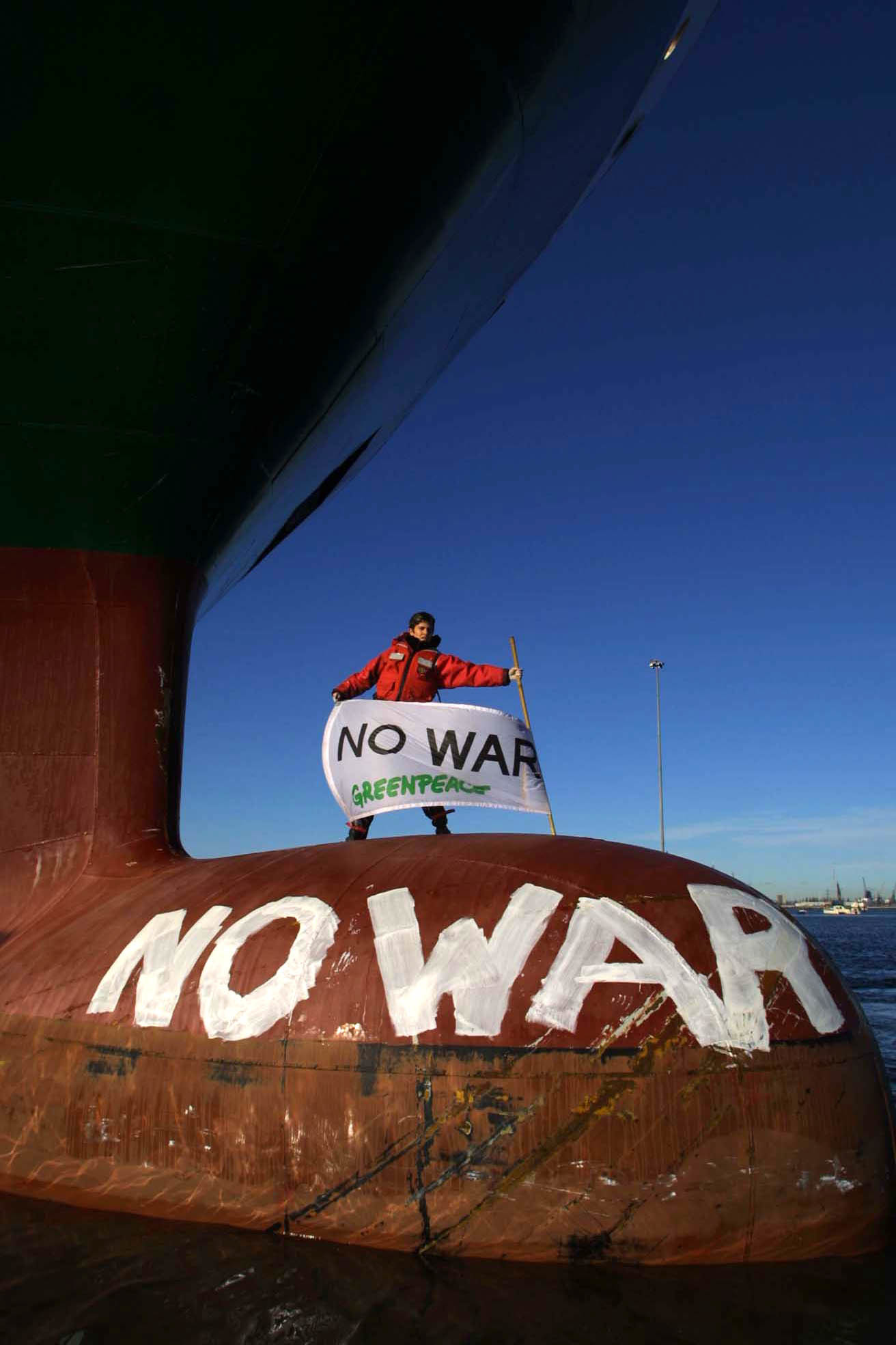 Activist with No War banner on a military supply vessel
