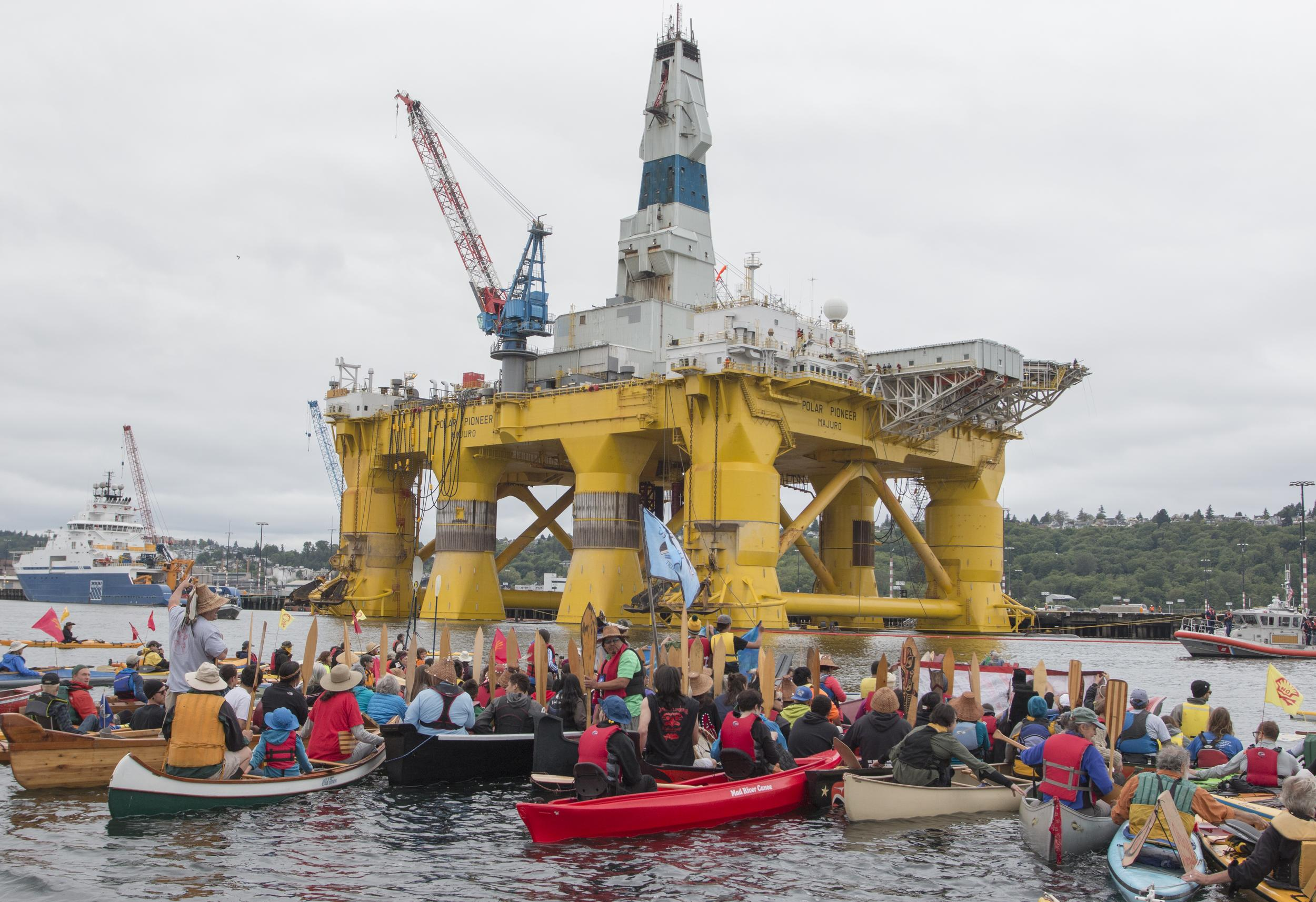 Small boats and kayaks surround a big oil rig