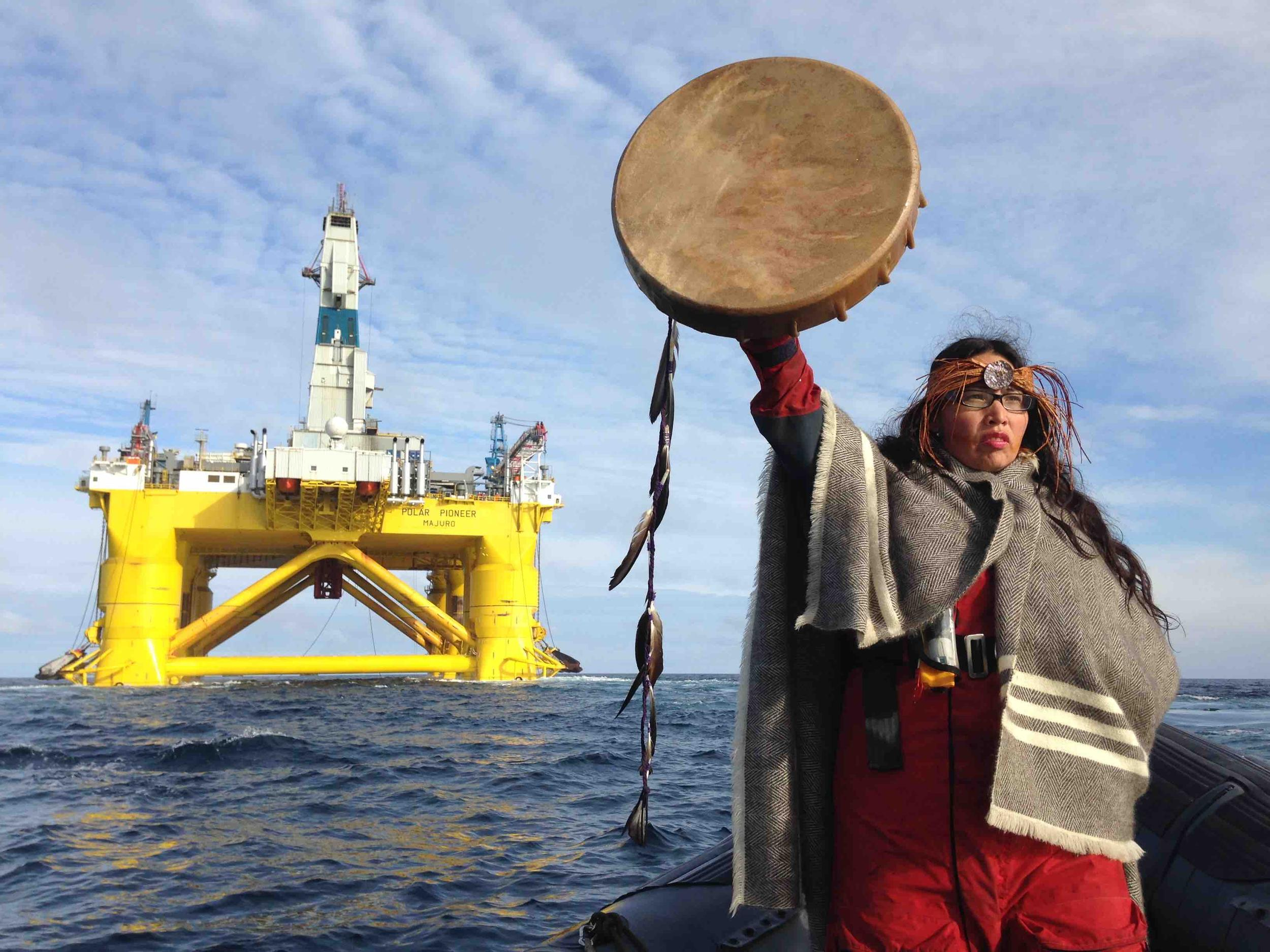 Indigenous Woman stands in rhib in front of oil rig holding a drum in the air