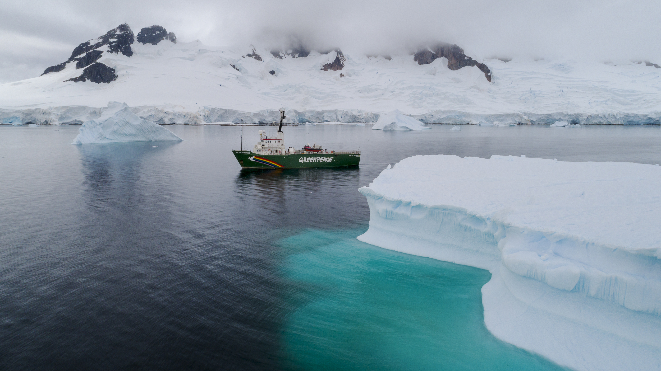 greenpeace ship next to ice in water