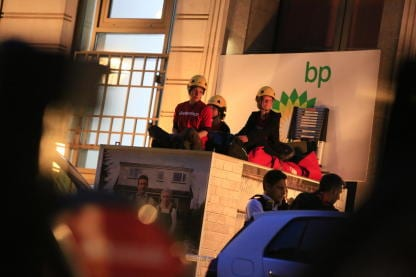 Three people sit on top of a box outside BP headquarters in London.