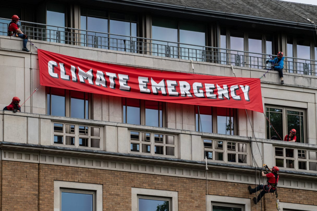 climbers with banner on top of building
