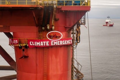 activists on oil rig with banner