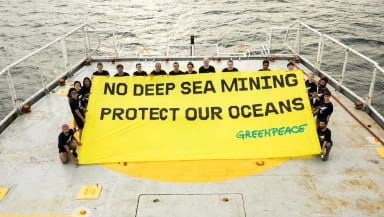 ship crew hold a banner on deck