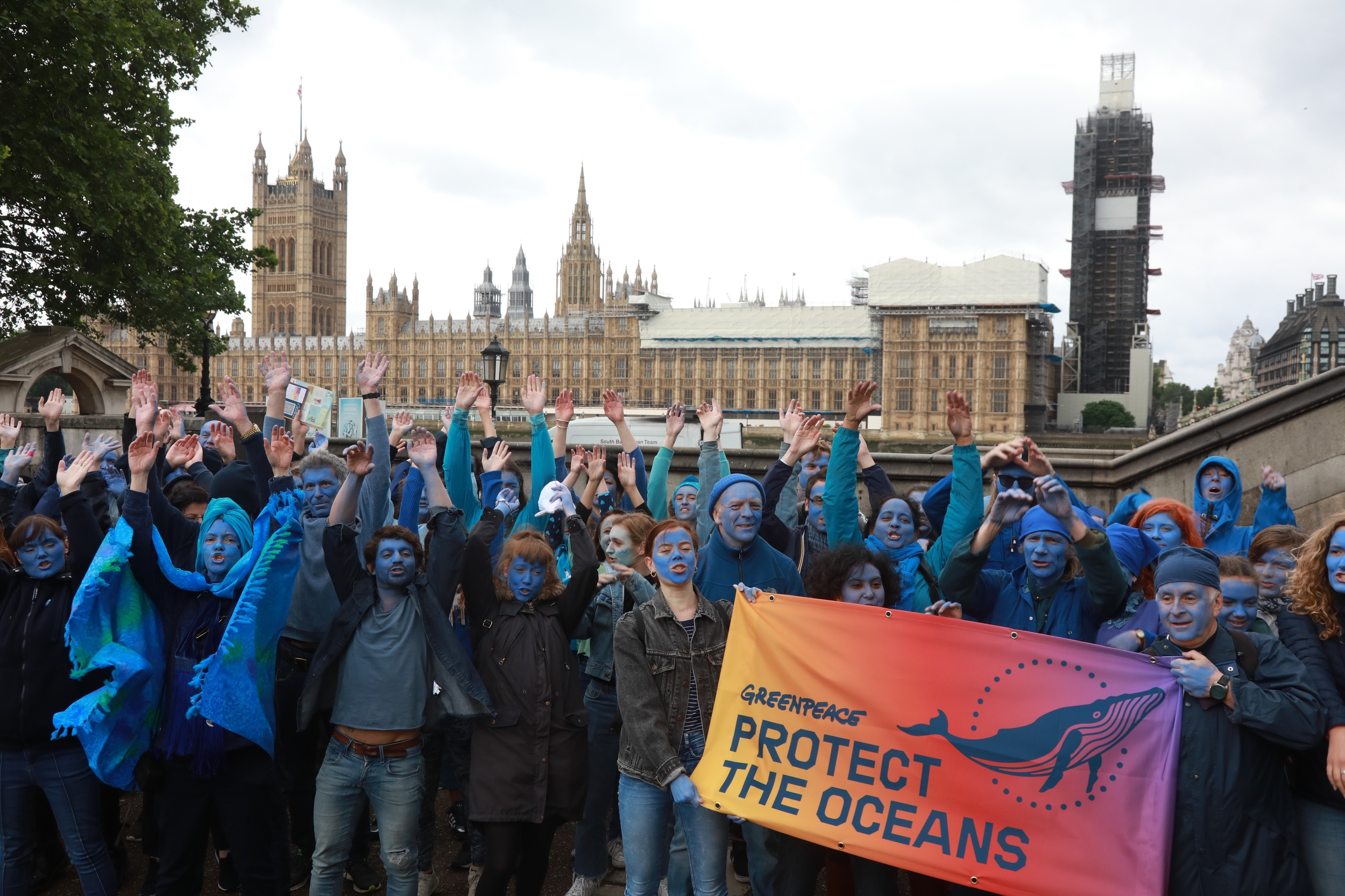 "Greenpeace activists with their faces painted blue in front of the Houses of Parliament with a Protect the Oceans banner waving their arms in a ""blue wave"""