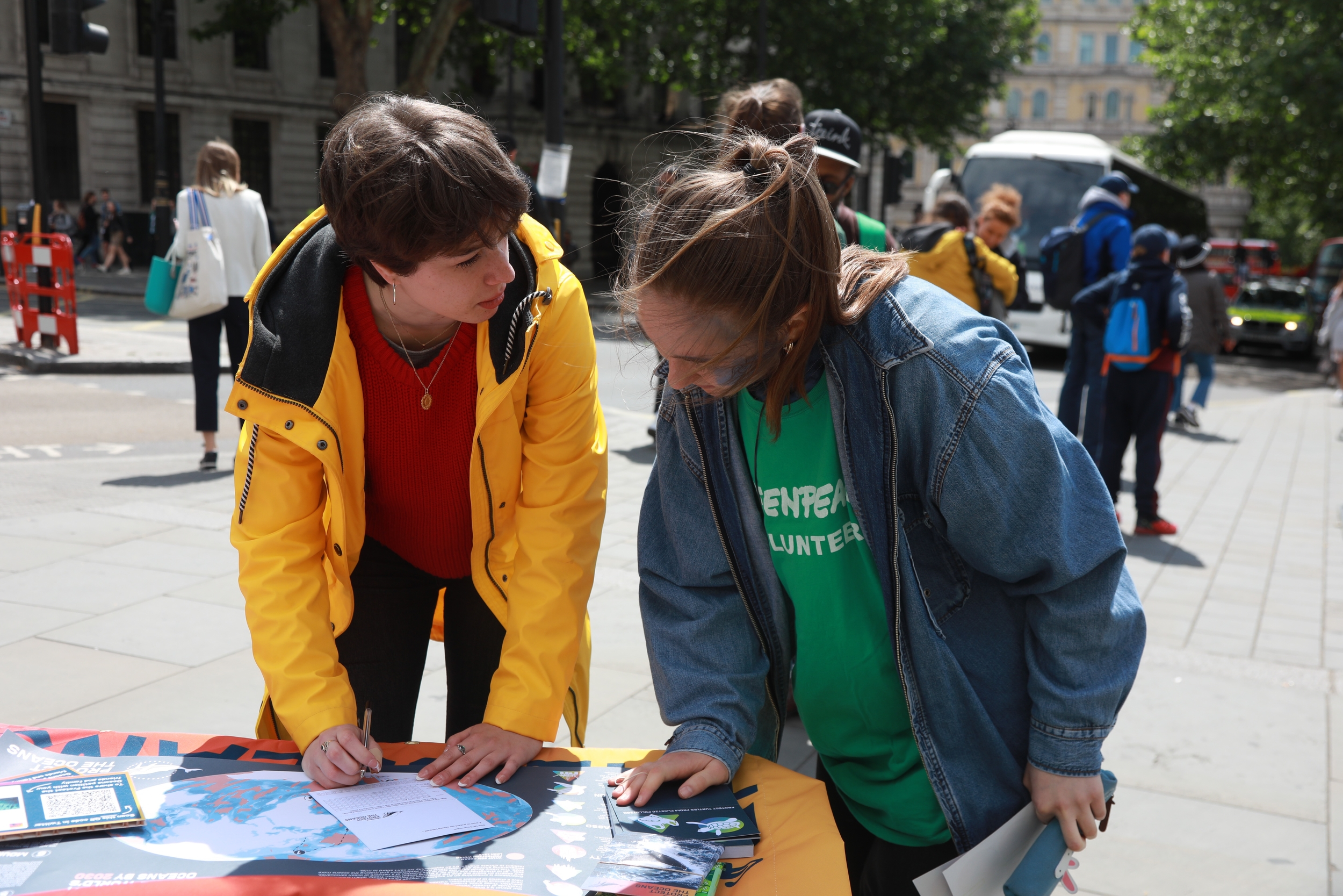A local volunteer chatting to a member of the public at their local group street stall