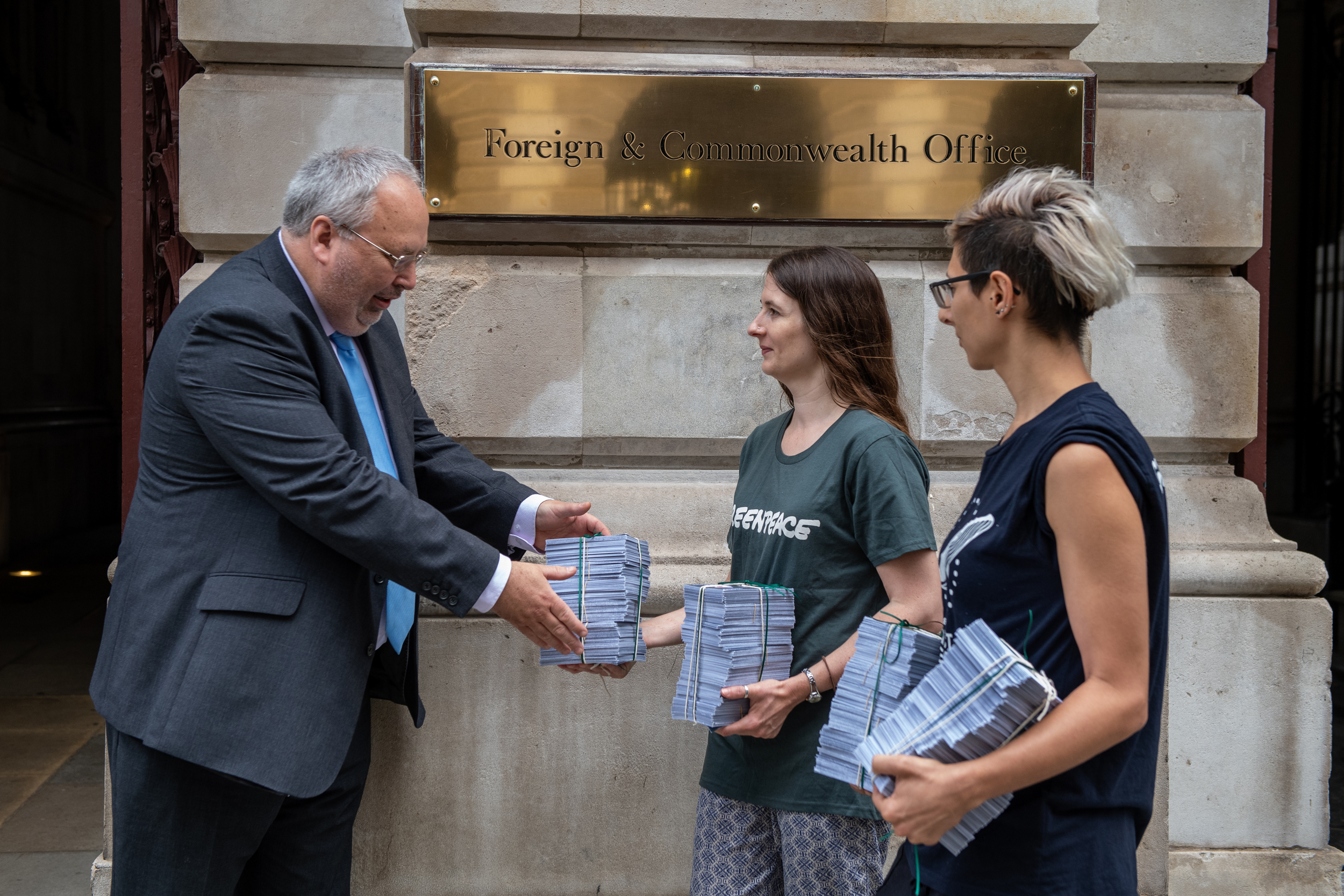 Local group campaigners delivering piles of messages to a UK Foreign Office official outside his office