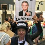 """Photograph of Greenpeace volunteer Nicole dressed in mourning at the London Climate Strike, with a sign reading """"Strike like a 16 year-old"""" with around an image of Greta Thunberg."""