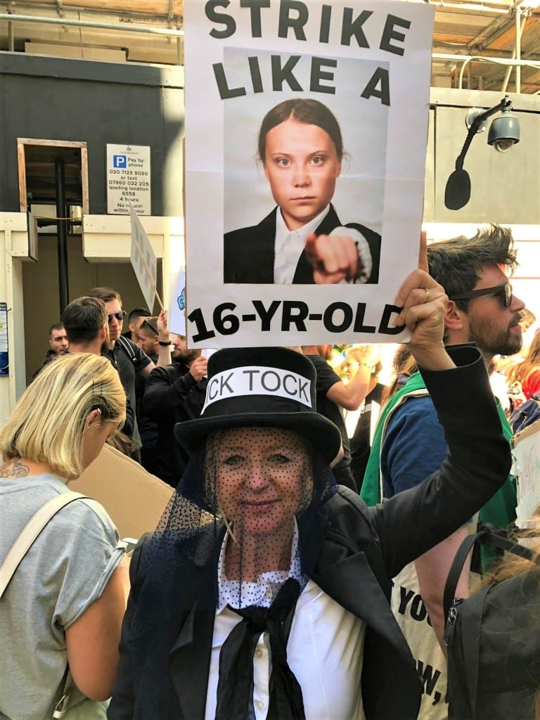 "Photograph of Greenpeace volunteer Nicole dressed in mourning at the London Climate Strike, with a sign reading ""Strike like a 16 year-old"" with around an image of Greta Thunberg."