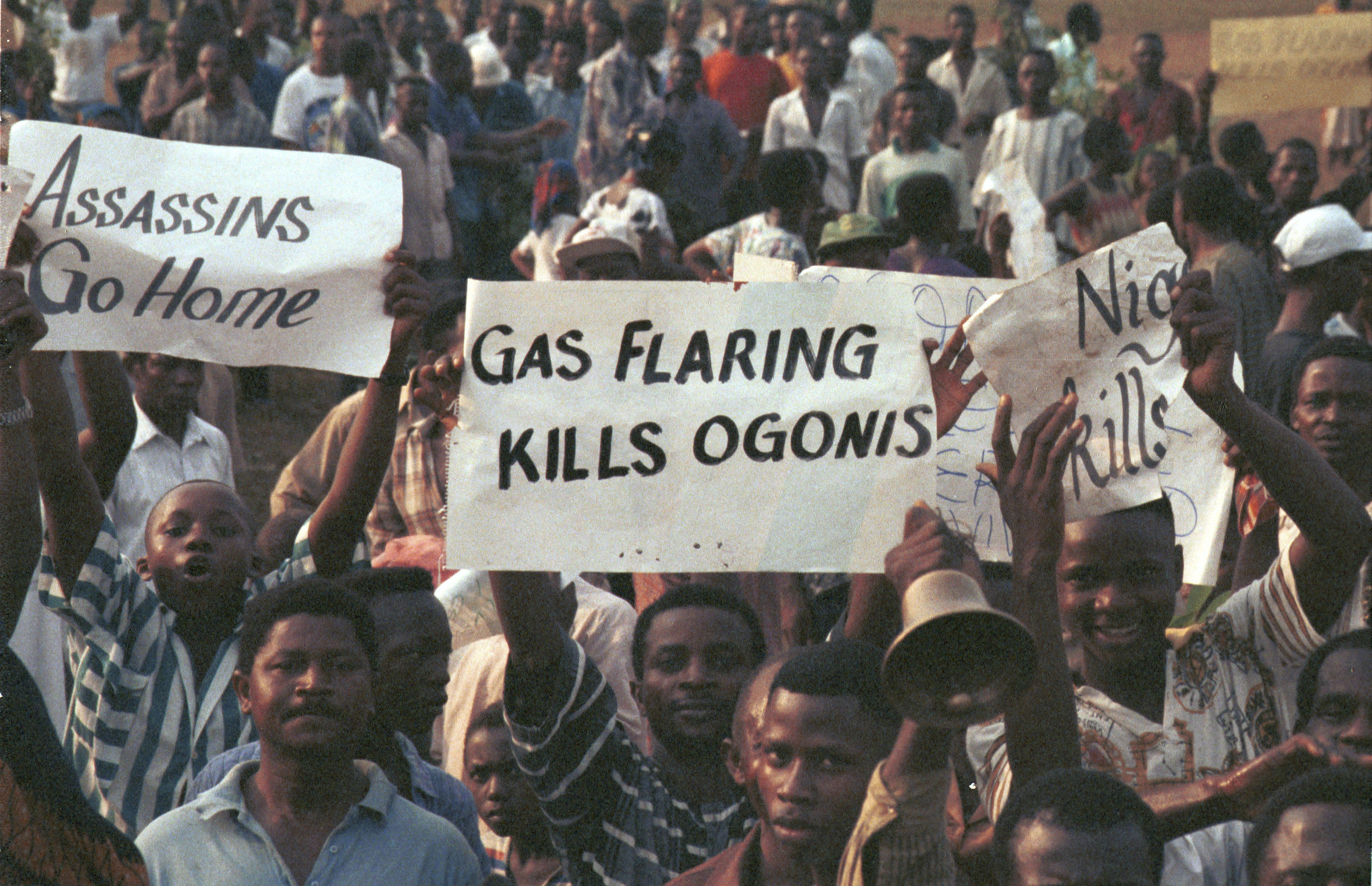"""High angel view of demonstrating crowd at Ogoni Day demo, with banners: """"Gas flaring kills Ogoni"""" and """"Assassins go home"""". Ogoni Day demonstration, Nigeria, 1993"""