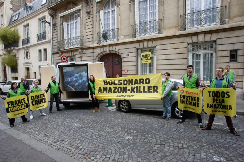"Protesters outside the Brazilian ambassador's residence in Paris with large yellow banners banners reading ""Bolsonaro Amazon Killer"""