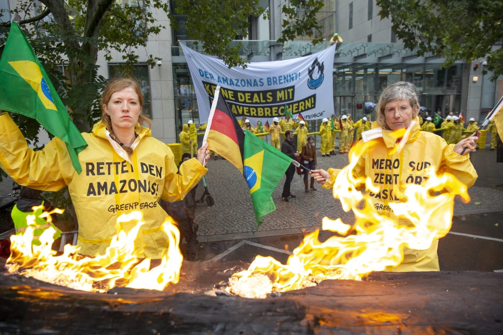 German Greenpeace protesters with burning tyres protesting Salles.