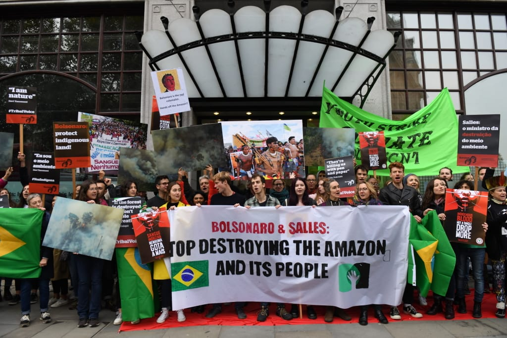 The UK Student Climate Network, Survival international and Greenpeace protest against the visit of the Brazilian environment minister, Ricardo Salles outside the Brazilian Embassy. They send a clear message to Salles that until his government's destructive agenda is reversed and the Amazon and its people are protected, he is not welcome here.
