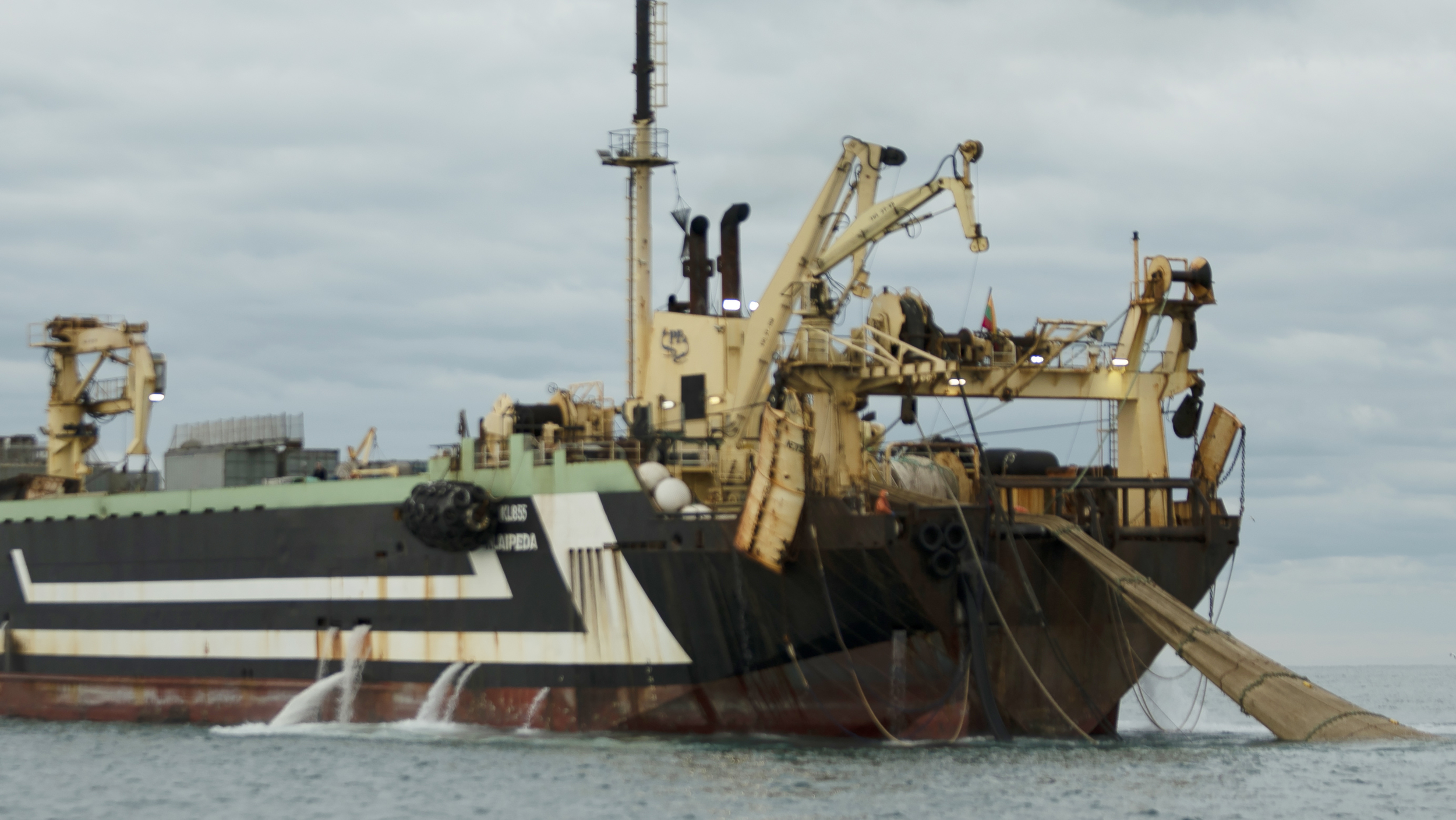 A huge fishing ship pulls in its nets using a rear-mounted winch