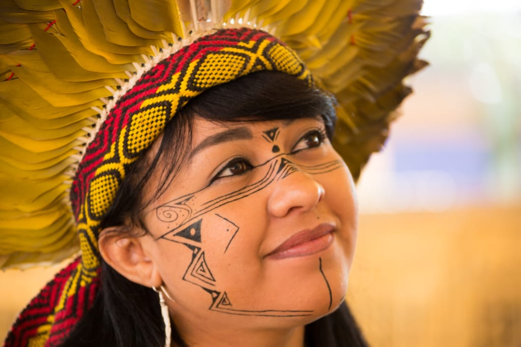 A picture of Célia Xakriabá with her face painted with Indigenous markings and a yellow feather headdress