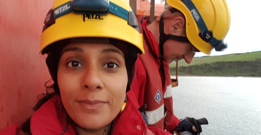 Meena on the oil rig with a yellow helmet and headtorch with Andrew behind her