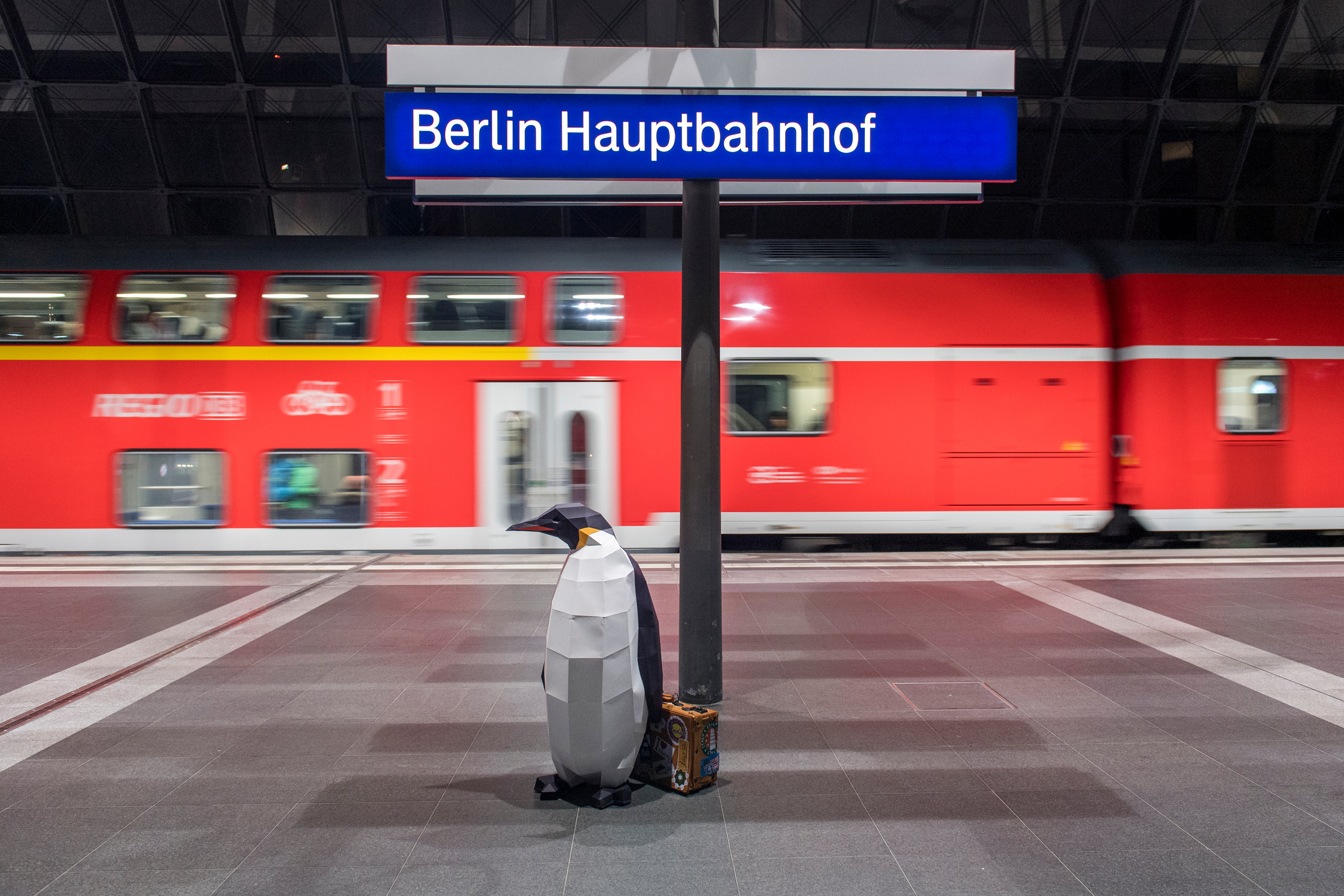 A paper model penguin with a suitcase on a train platform in Berlin.