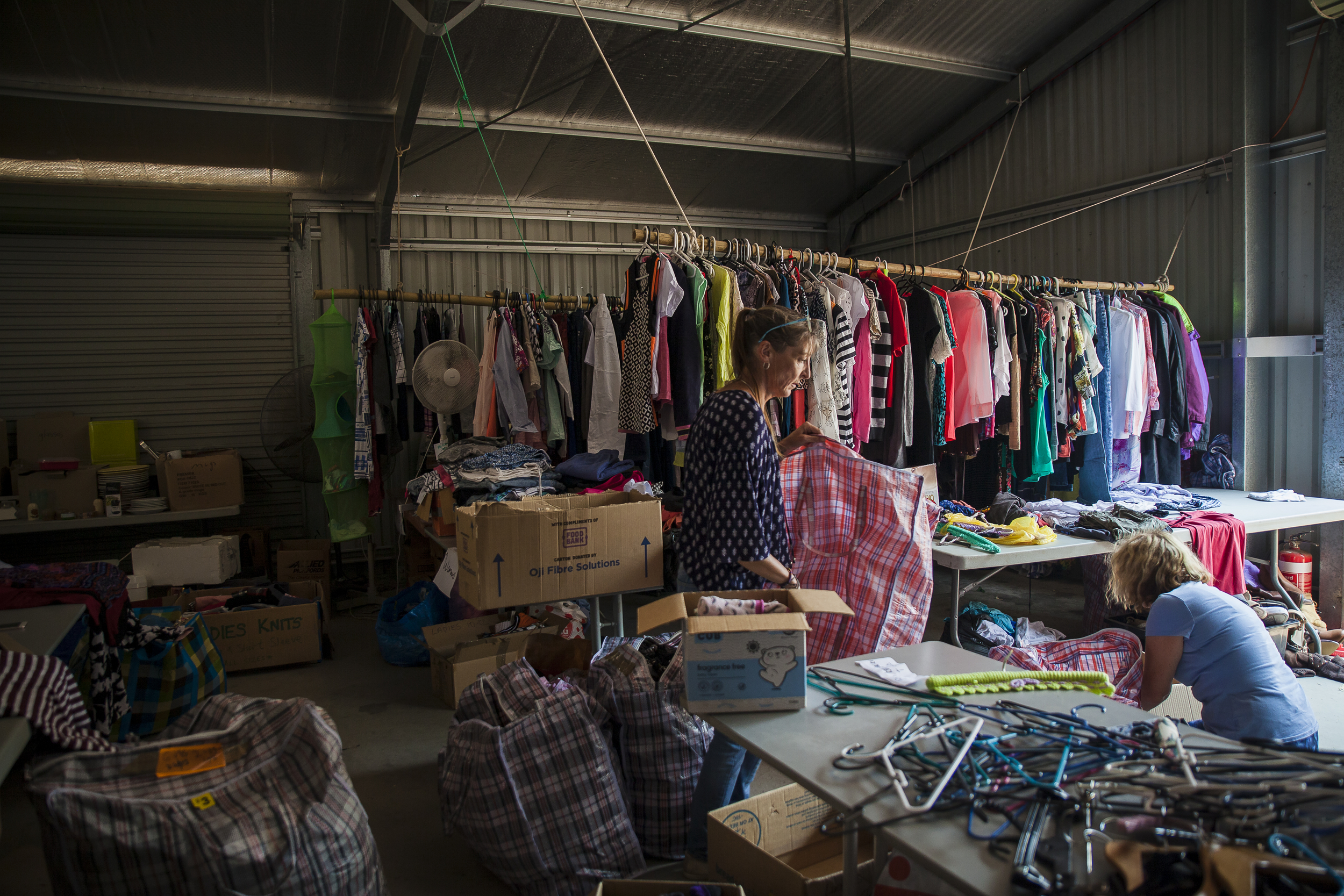 Community centre with clothing hung on rails and women sorting donations.